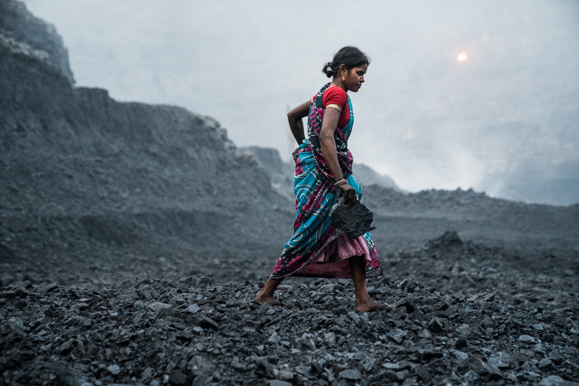 A female coal miner scavenges for coal deep inside a mine in one of India's largest coal mining regions in the state of Jharkhand.