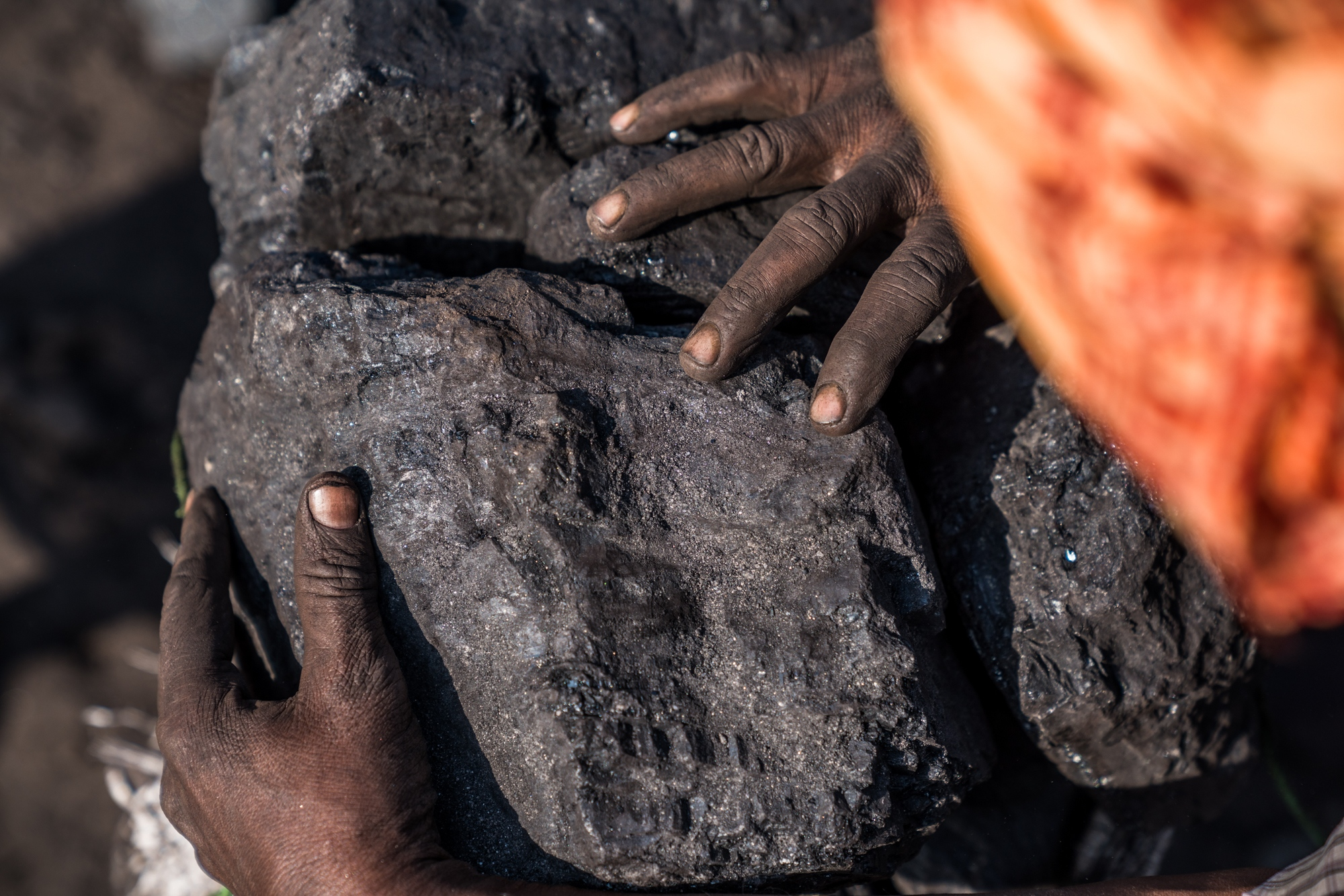 A coal miner making sure the blocks or coal are securely placed inside the stack before it is transported away for sale or personal use.