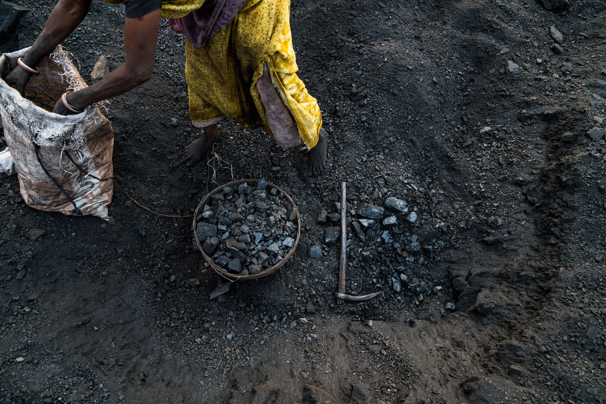 A basket full of coal amongst a coal miners tools. This coal will be transported to be sold or used personally as cooking fuel. India.