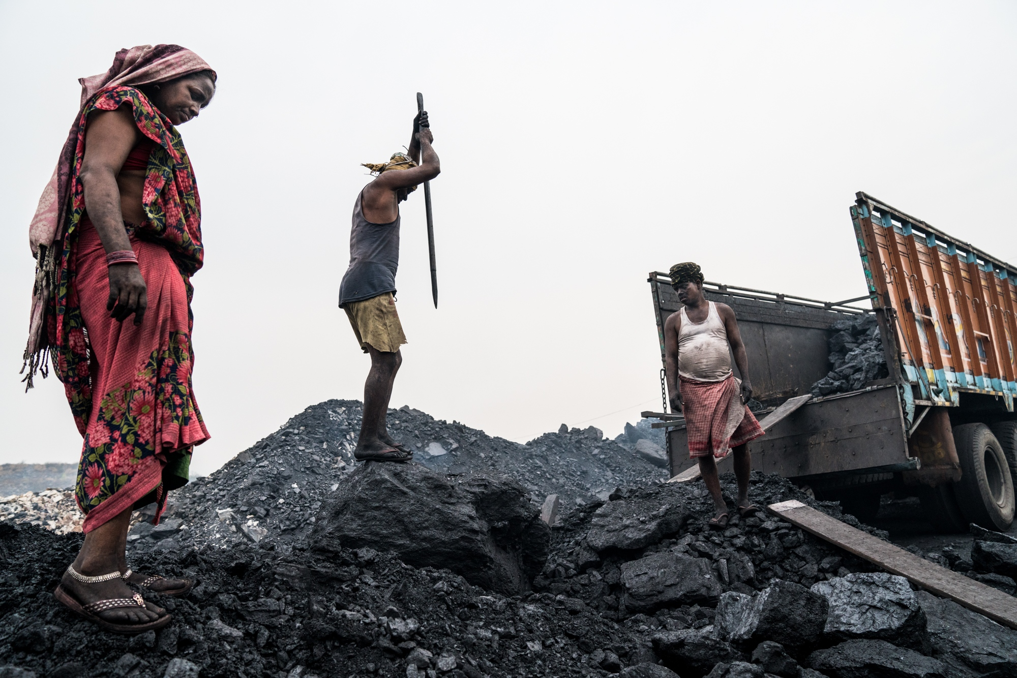 Miners break apart coal for large scale transport to use as fuel in power plants across India that spit out vast amounts of black carbon and other particulates for electricity production.