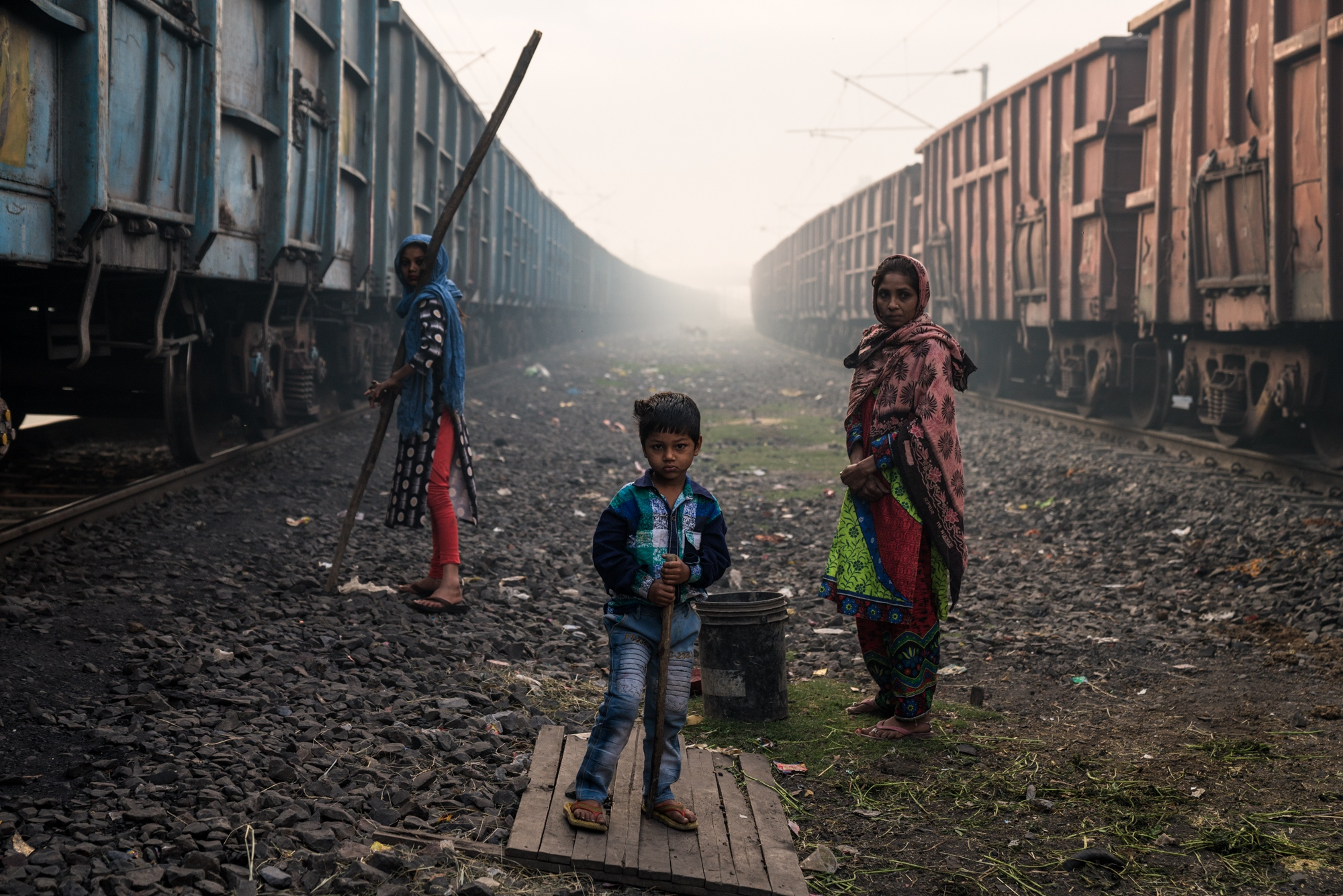 A mother and her two children wait for the trains to halt; after they will break into the carriage using the long stick to steal left-over coal for cooking fuel. Central India.