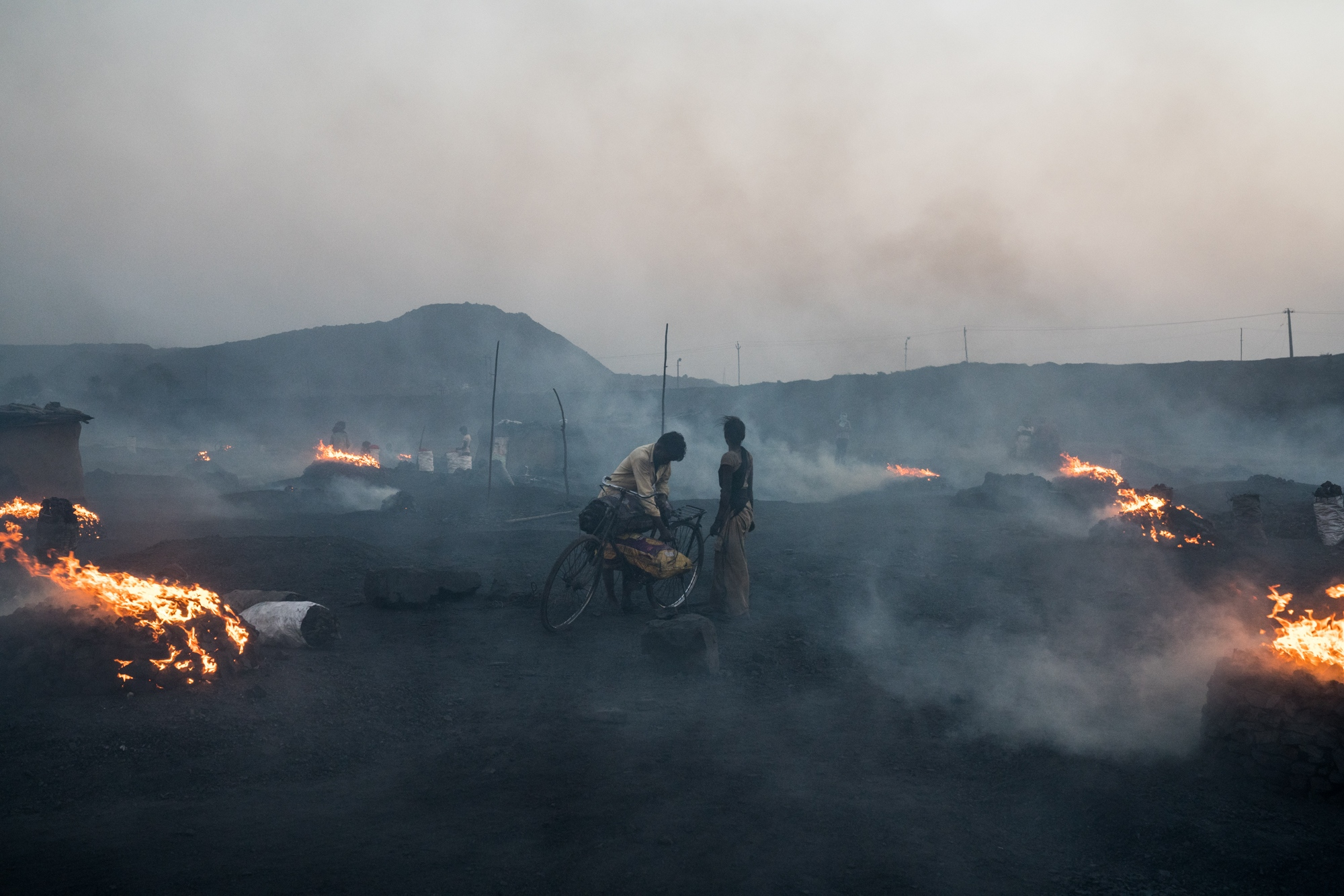 Miners off-load coal in a charcoal-producing area, which constantly blankets the region in thick smoke. India.