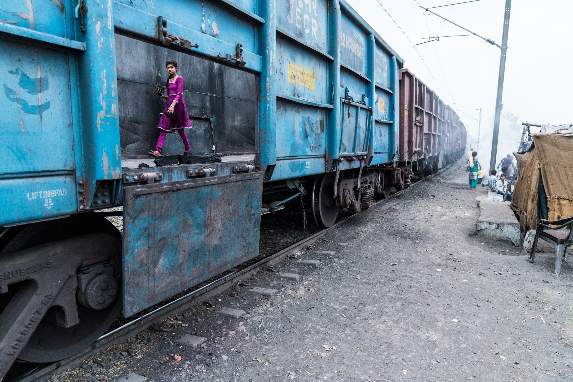 A young girl stealing left-over coal from a coal-train carriage to use for cooking fuel. India.
