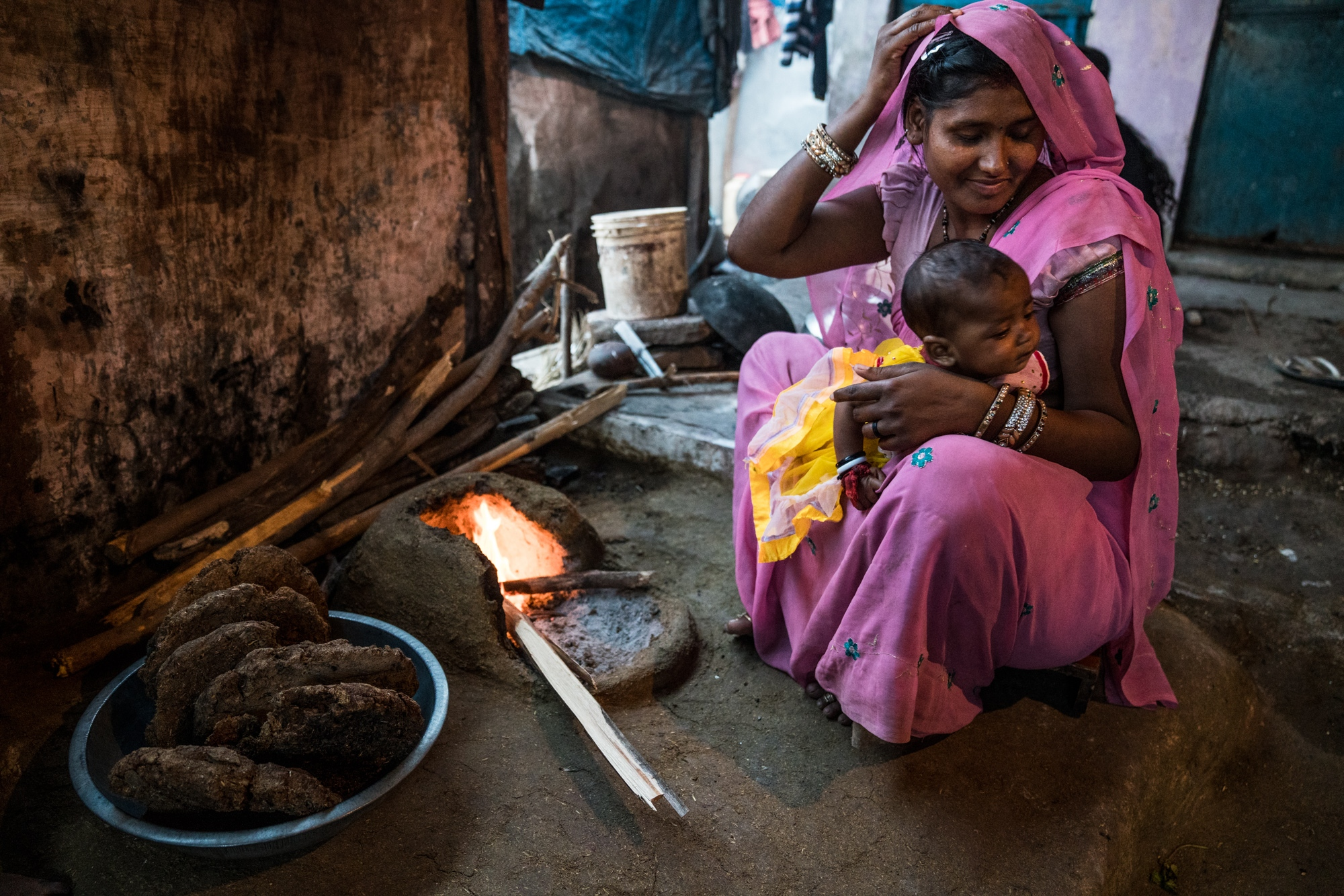 A woman with her baby prepares a fire before cooking dinner using a mixture of dung and wood as fuel. India.