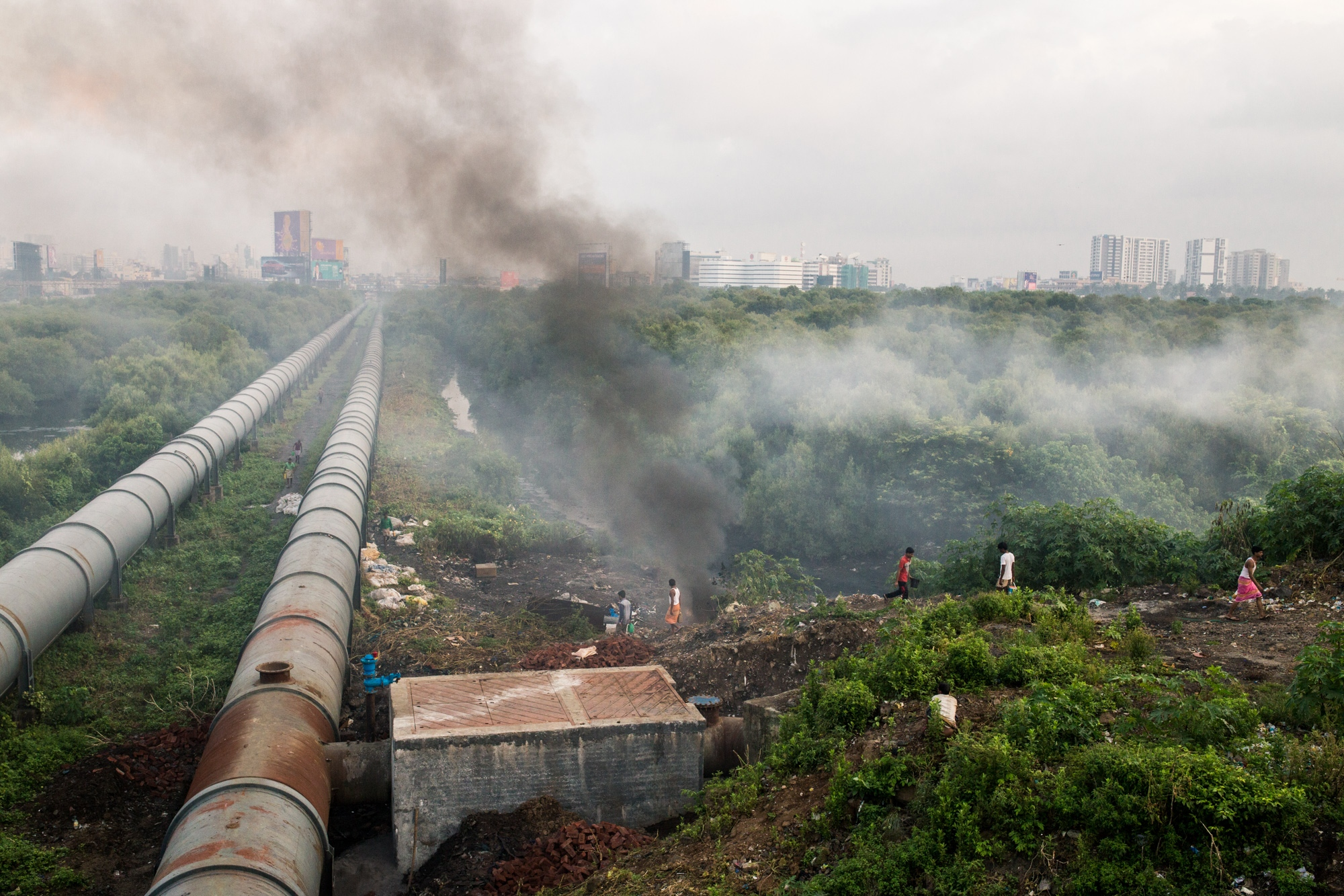 Smoke rising from a burning garbage dump releasing deadly chemicals from plastic and black carbon from organic material in India's metropolitan city of Mumbai.