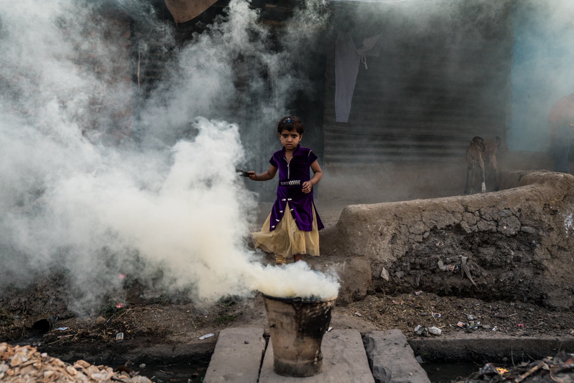 A girl emerges from the coal smoke of her family's chulla before dinner time. India.