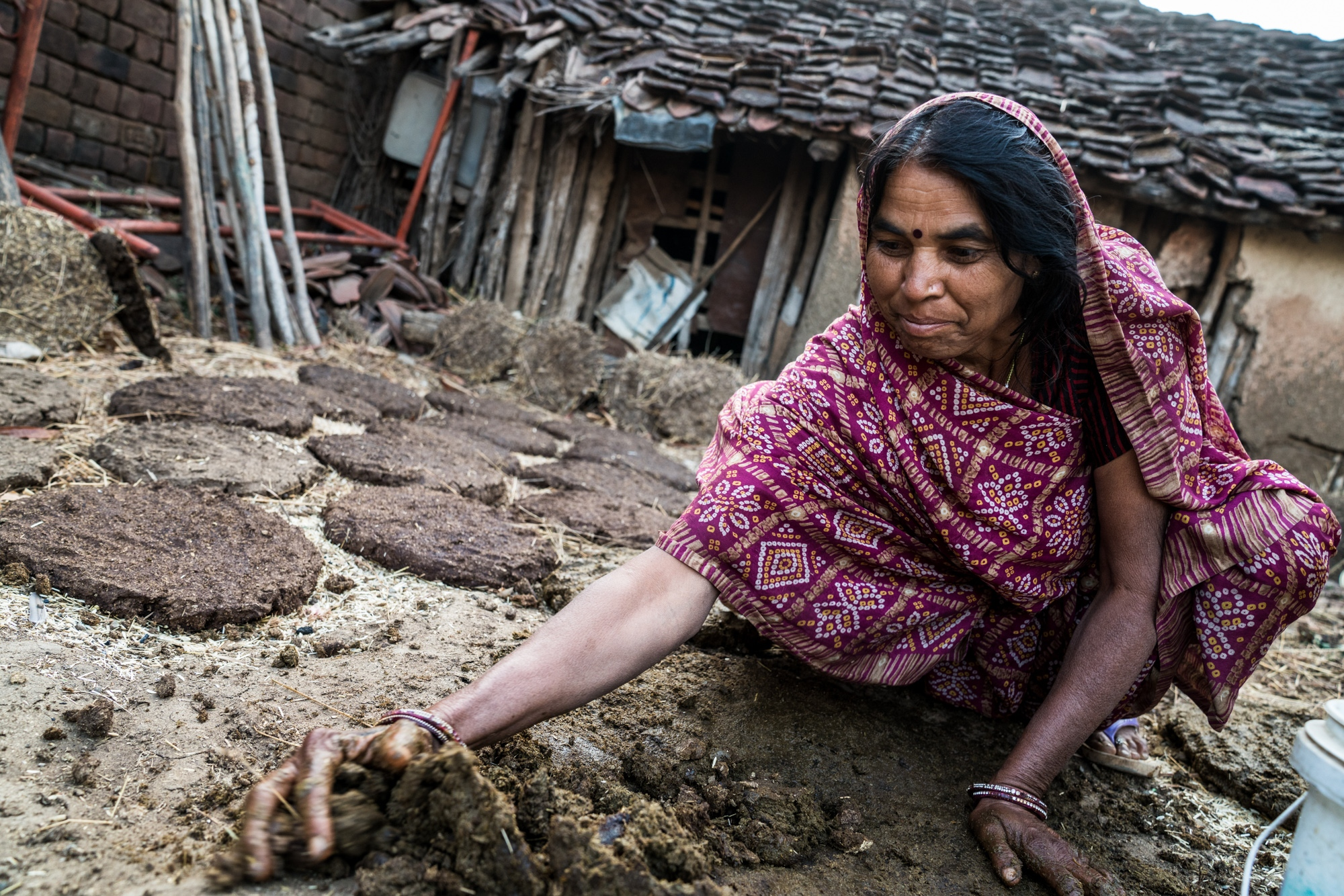 A woman putting together freshly collected dung to be made into dung patties, which will, in turn, be used for cooking fuel.