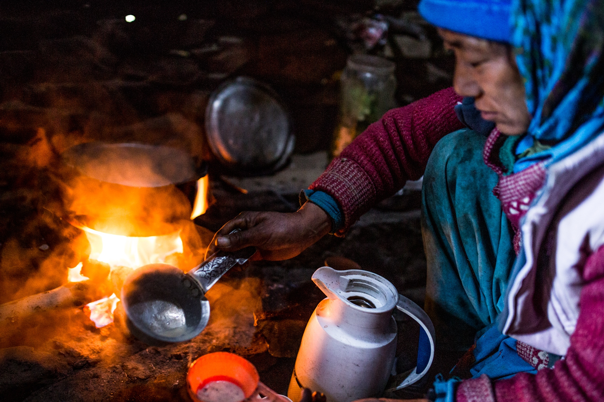 A dung-fuelled fire used to boil water to prepare chai in a smoke-filled kitchen. India.