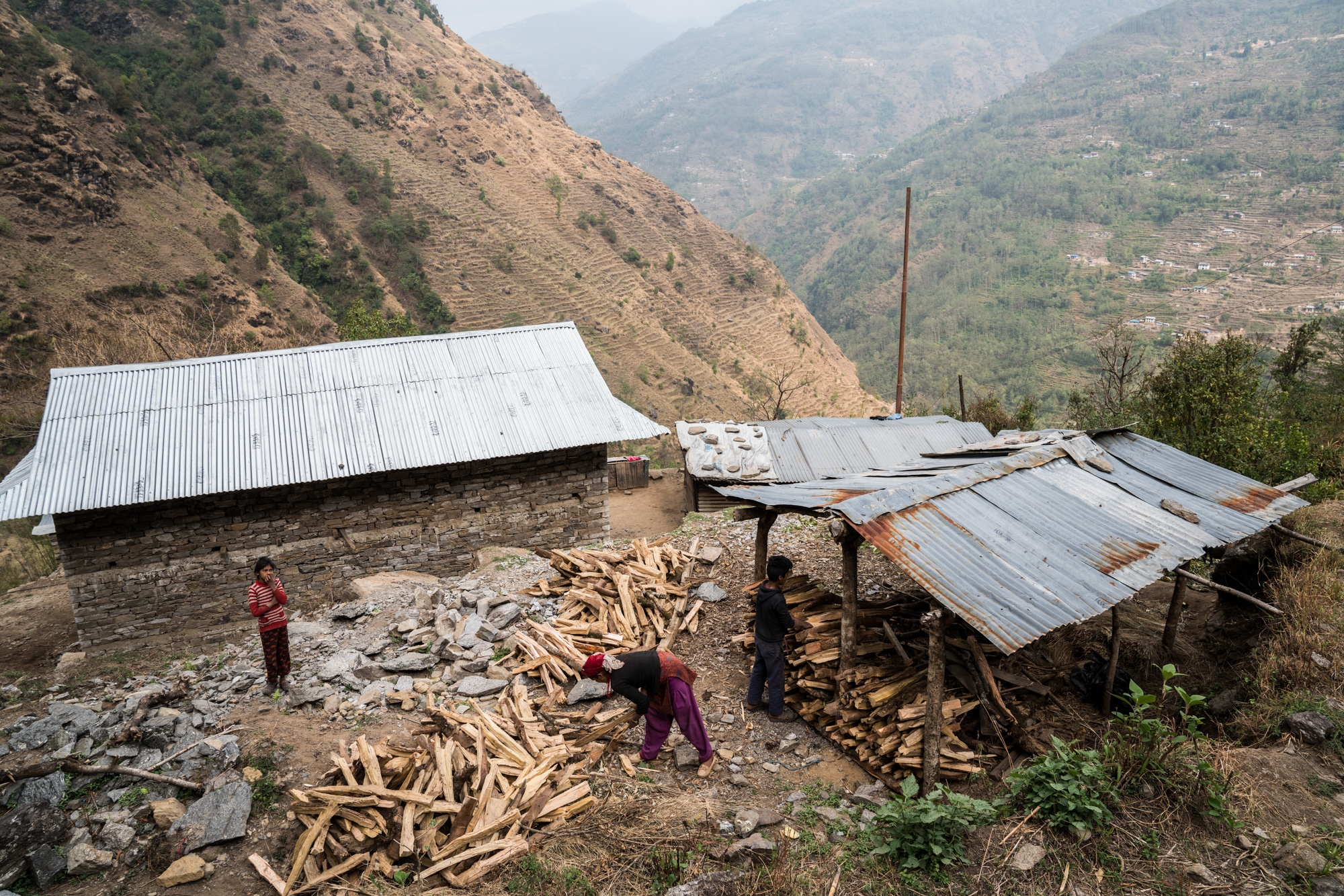 A family cut and store firewood, for cooking, which has been sourced from already deforested parts of the Nepali Himalaya.