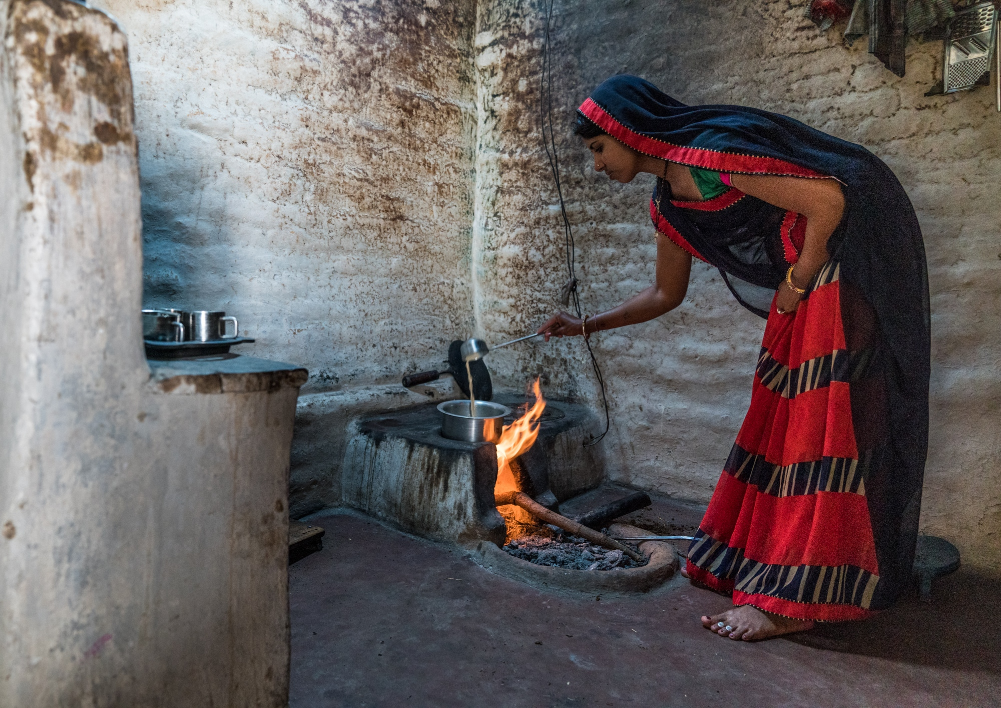 Soot stains the walls of a rural kitchen where a woman prepares chai fuelling the fire with a mixture of wood and dung. Central India.