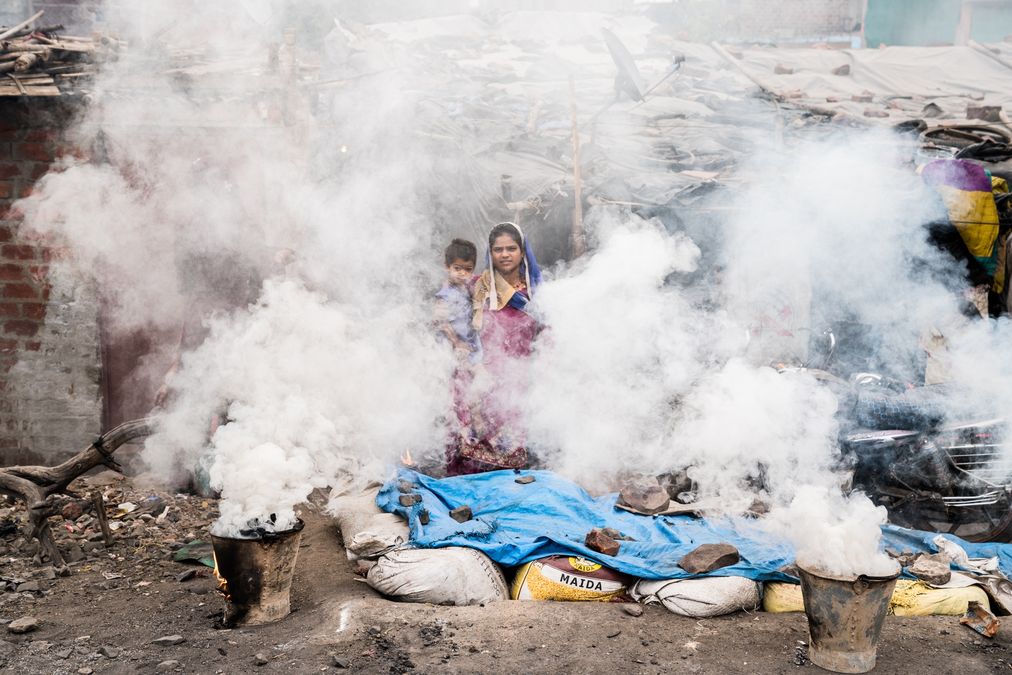 Surrounded by smoke, this is a daily occurrence during meal preparation time for this mother and her newborn, both subject to breathing in deadly particulates such as black carbon. India.