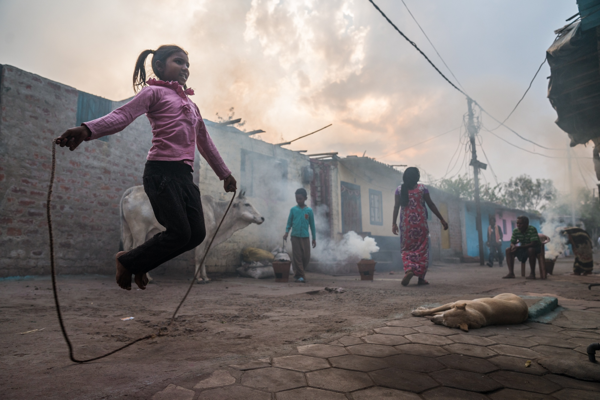 Skipping inside a slum settlement while smokey chullas burn coal, dung, and wood before they are used for cooking dinner. India.