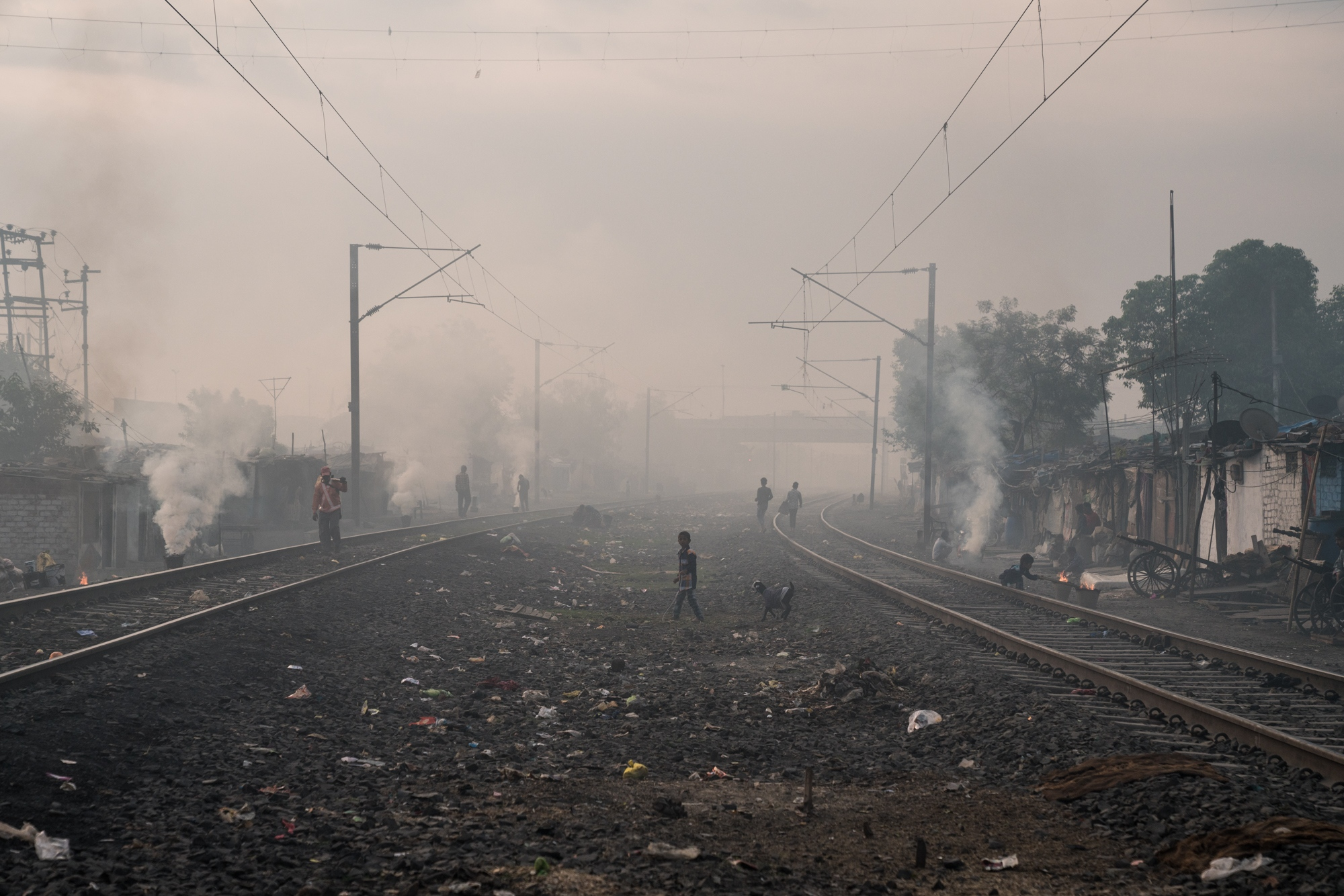 Smoke from hundreds of cooking fires blanket an urban area in Central India creating a brown haze during dawn.