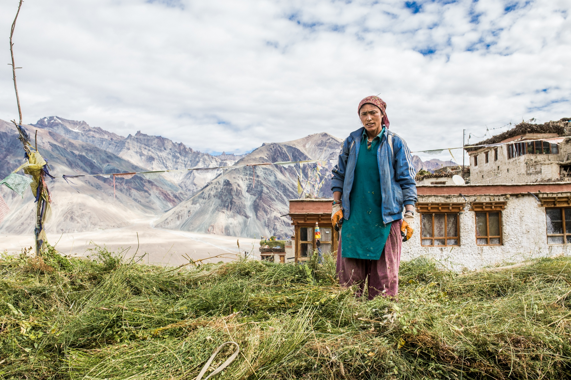 Tsewang Zangmo stands on top of her home and the fodder used to feed livestock during winter. Limited water supplies are reducing the amount that can be grown and, at times, is critically lacking. Kumik, India.