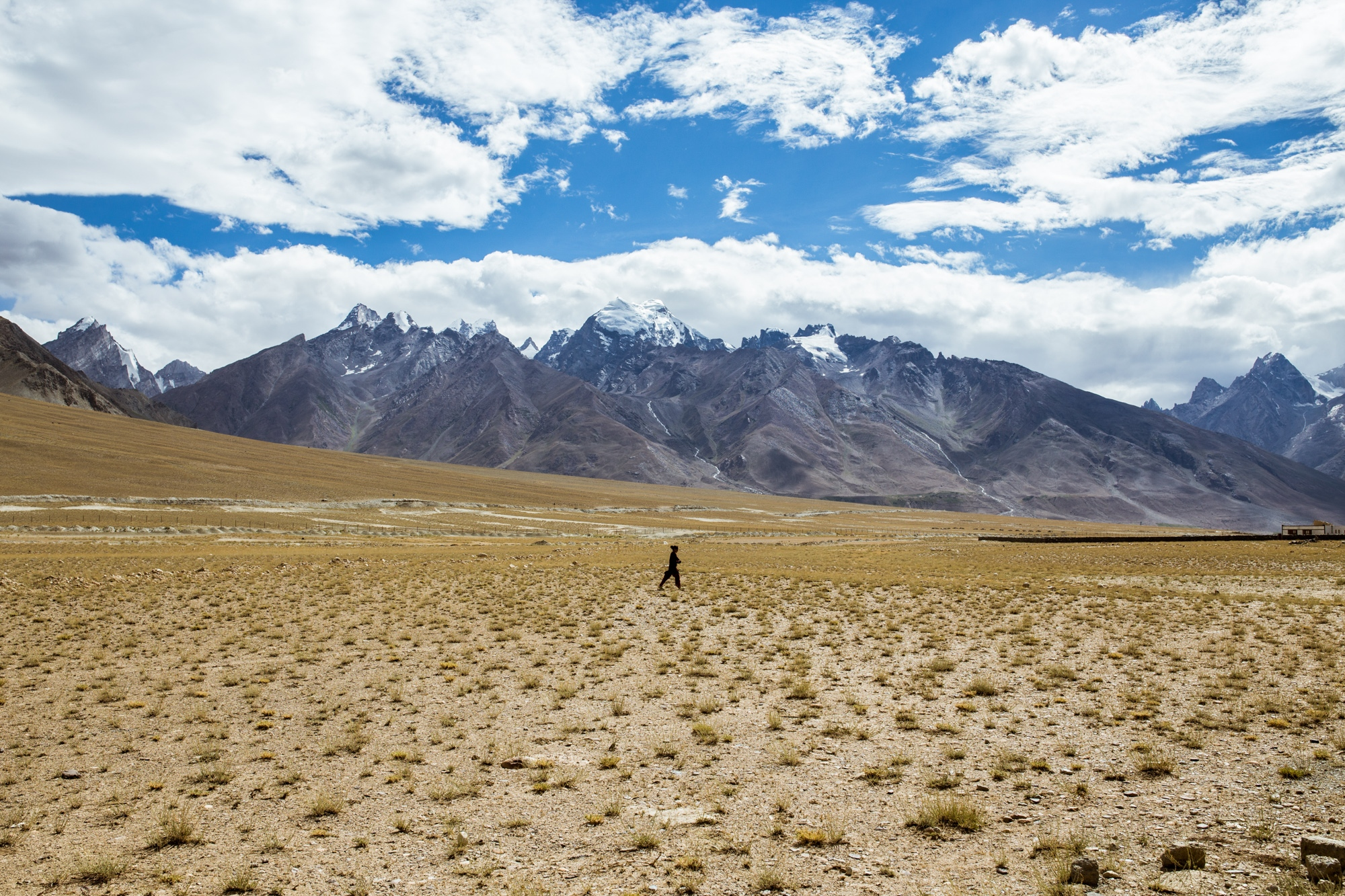 A woman walks home along the barren landscape in the Zanskar Valley, India. This area was chosen as a relocation zone for the village of Kumik due to water shortages in their old village. However, the new area faces similar issues.
