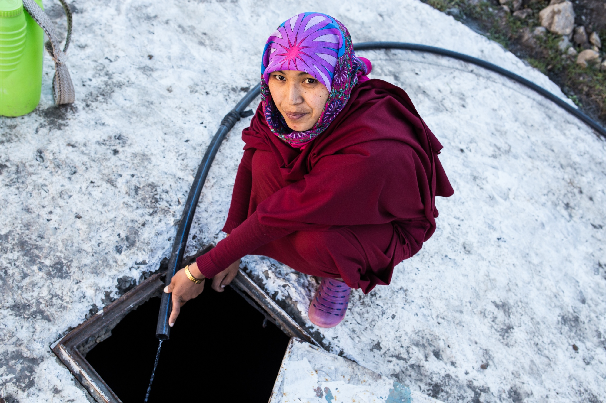 A Buddhist Nun in India's Spiti Valley inspects a trickle of water from their dying spring nearby the Nunnery. They now have to walk to the next village to retrieve water where they mentioned communities are now arguing about water allocation.