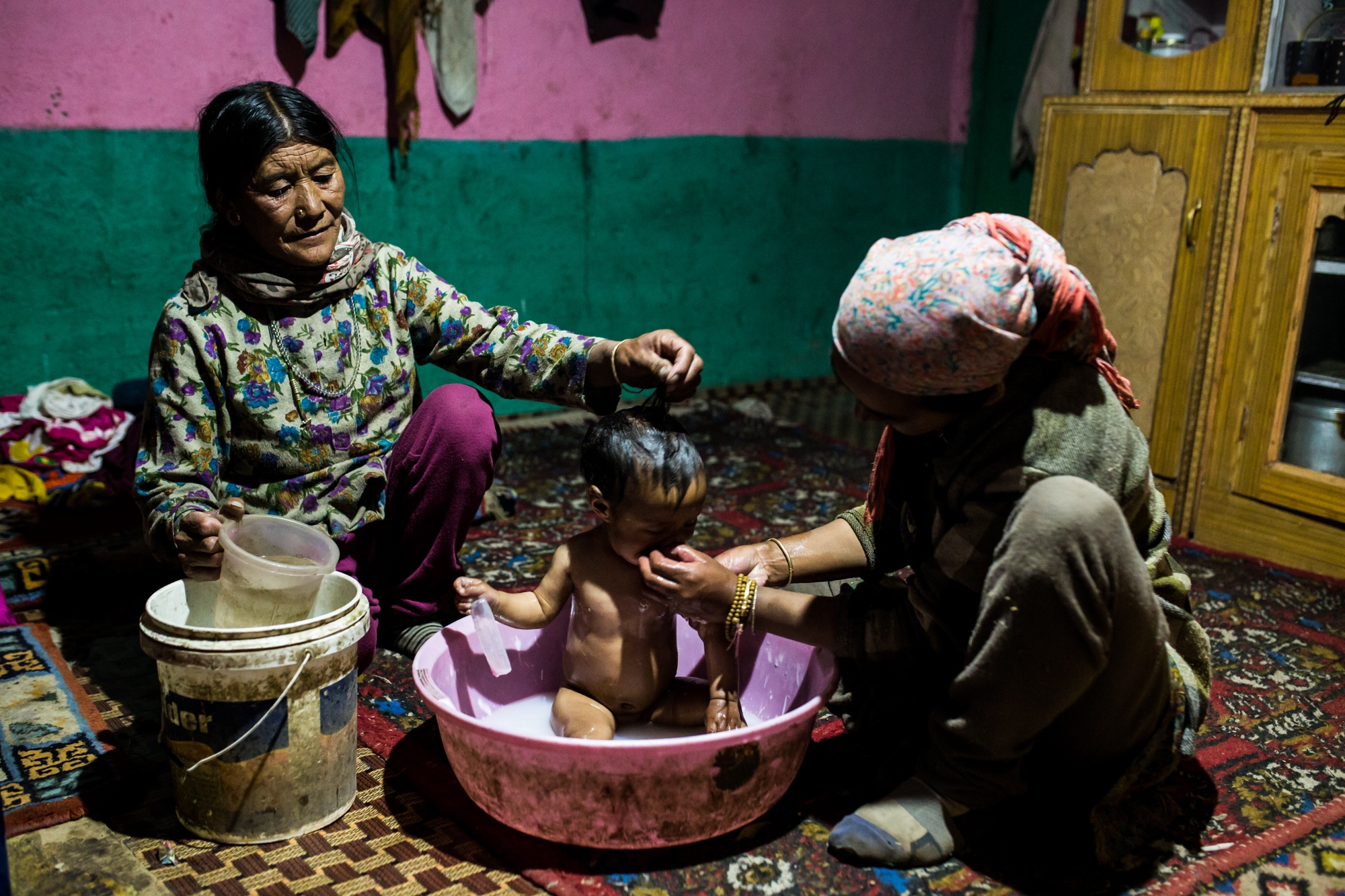 A newly born baby being bathed by grandmother and mother in the water-stressed Himalayan village of Kibber, India.