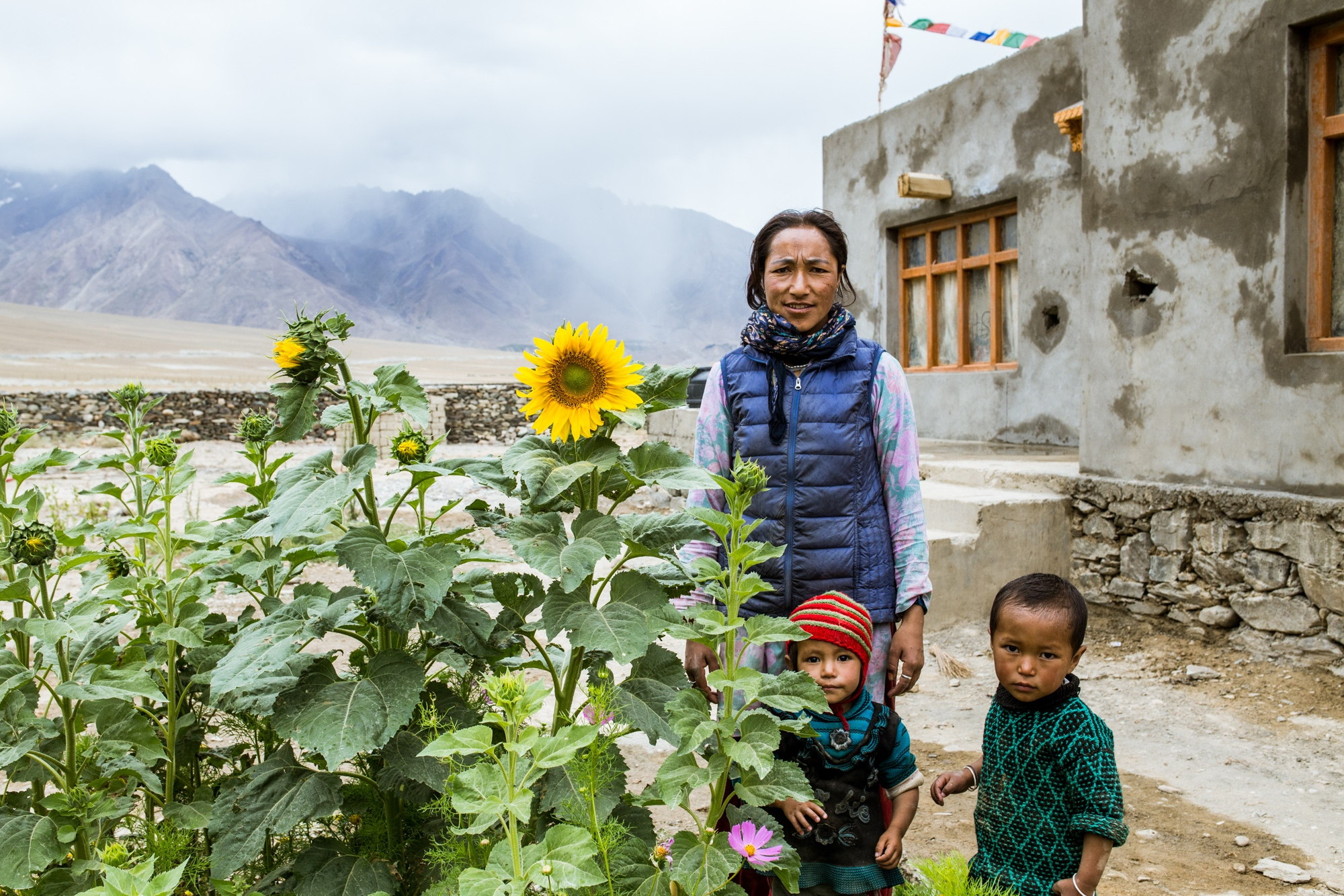 Tazen Chezen and her children stand in front of their new home in the Zanskar Valley, India. Tazen's family moved in search of water, as their previous home in Kumik faces constant drought due to the old glacier disappearing from warming temperatures.