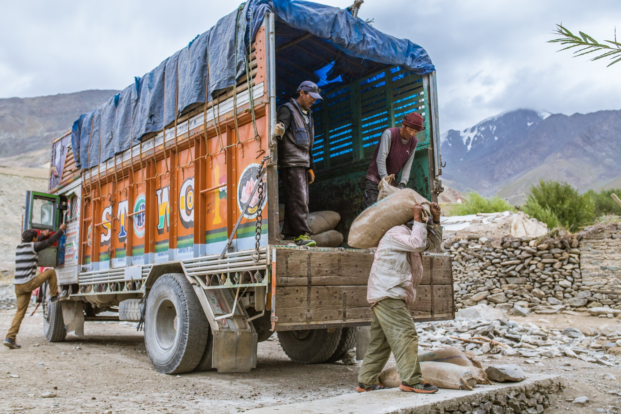 A man carries imported food to a storehouse in the water-stressed village of Kumik, India. As Kumik's glacier has fully retreated due to black carbon and climate change's warming impacts, the village is unable to produce enough crops because of water shortages. More food is now imported in diesel-powered trucks.