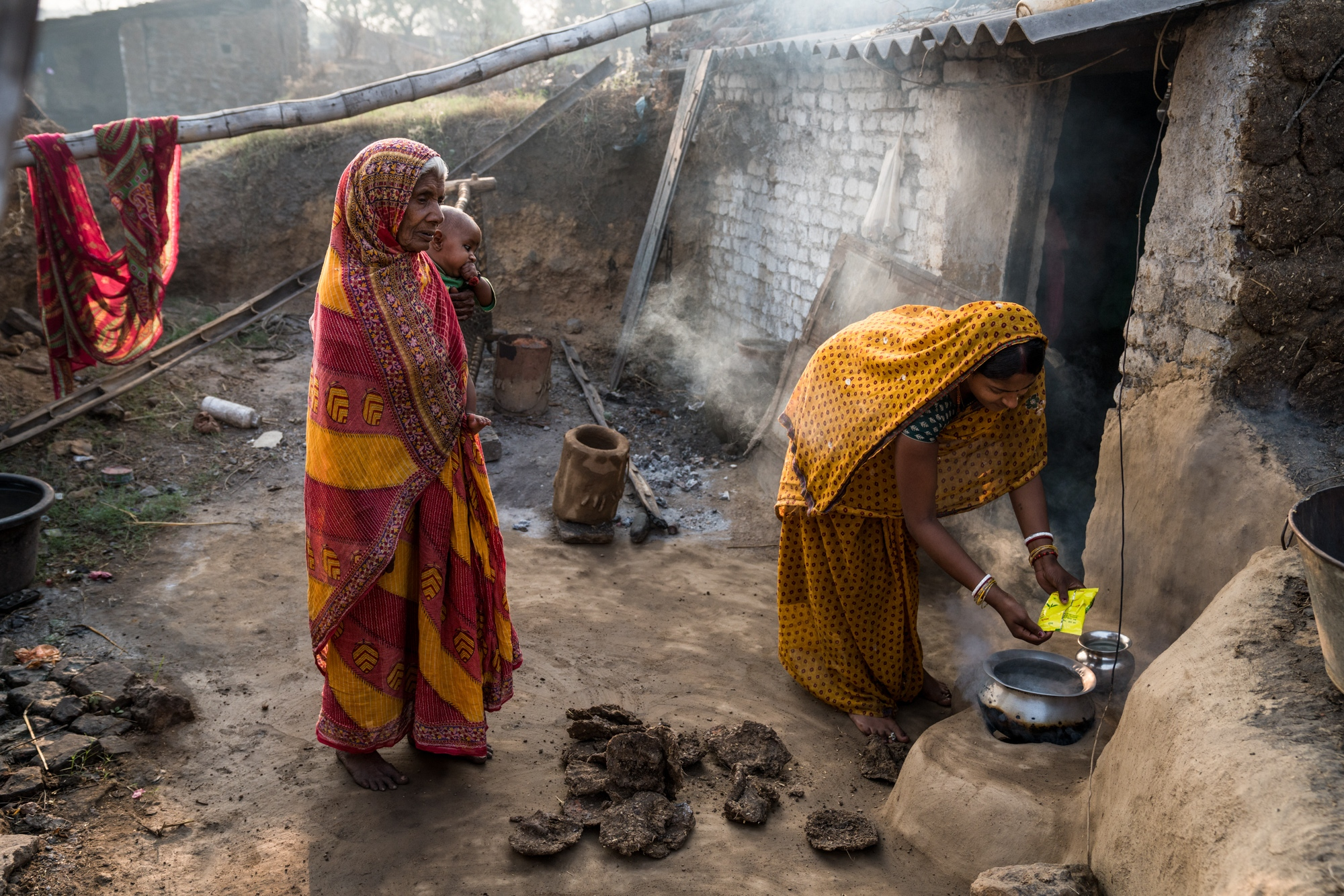 Grandmother and her grandson look on as the mother prepares a boiled breakfast using dung cakes in Jharkhand, India.