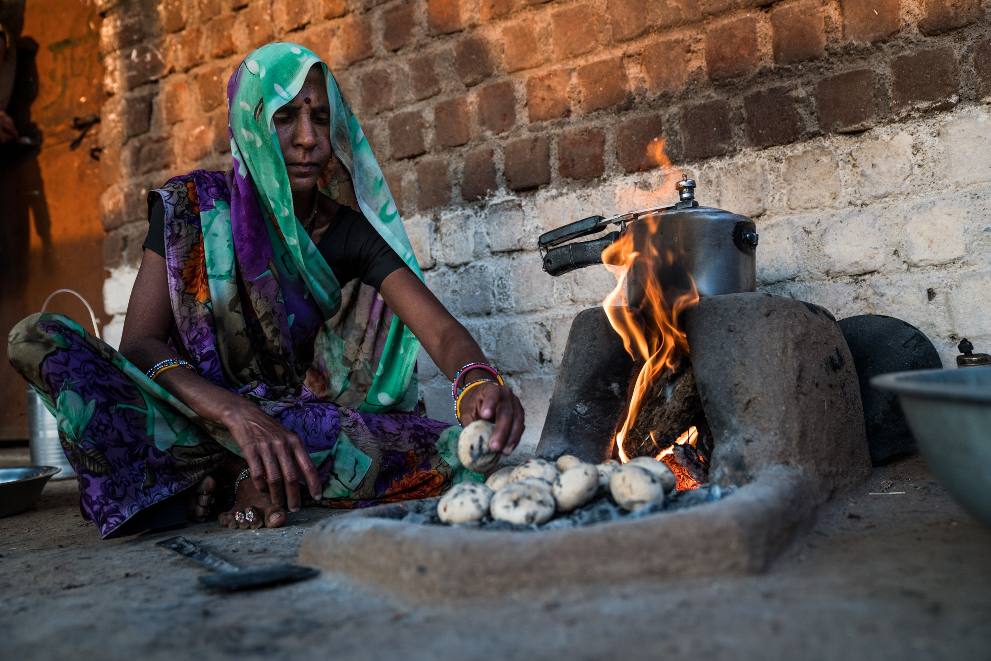 A woman prepares dinner from a dung-fulled fire in Central India.
