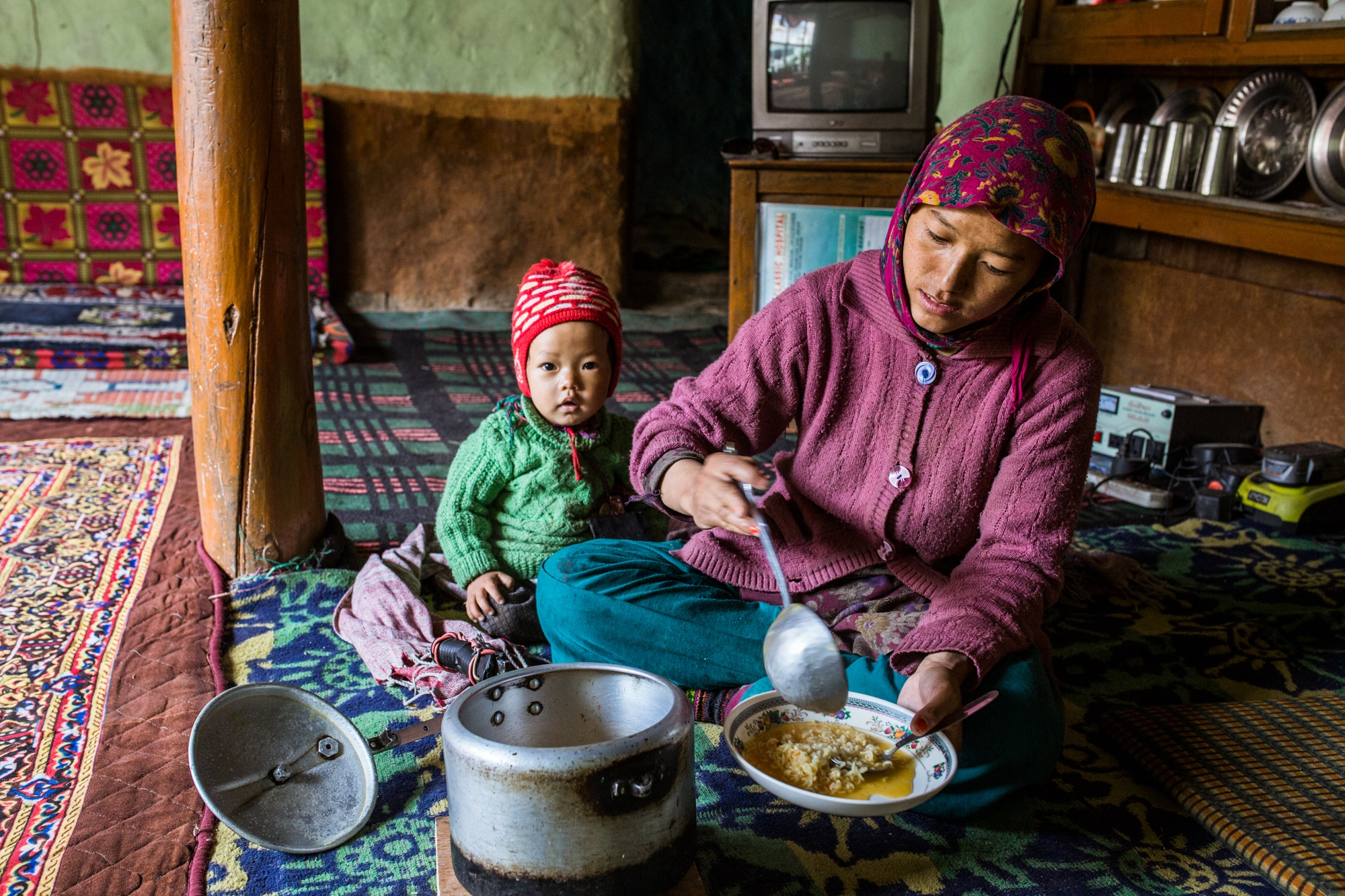 A mother serves a meal of imported instant noodles inside her home in the Zanskar Himalaya, India.