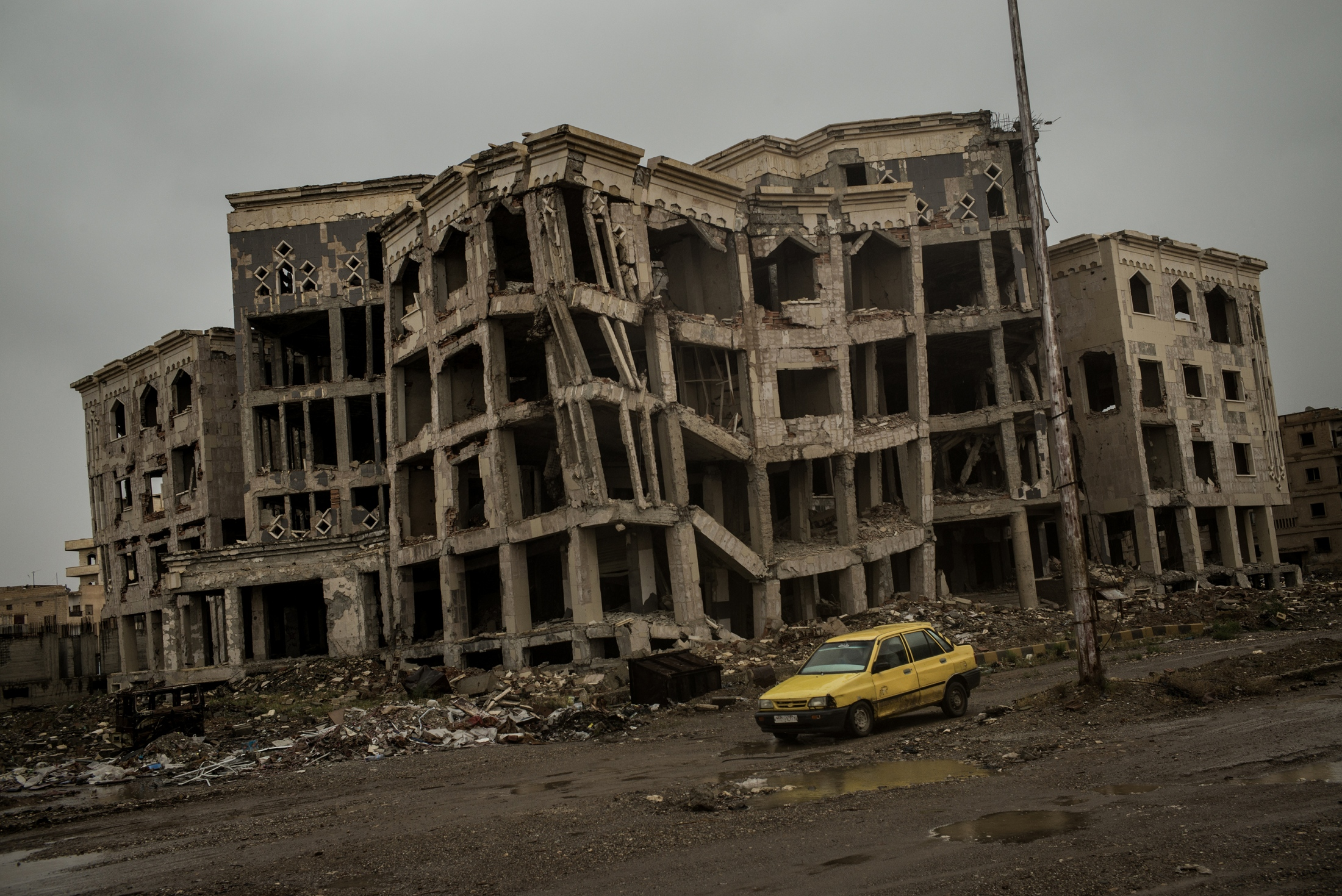 A view of damaged buildings seen through the rain, in Raqqa, Syria, on Friday, May 11, 2018. Seven months after ISIS was ousted from their capital, civilians are returning to rebuild their lives and homes. Without a visible presence of NGOs or strong support from the coalition because of ongoing security concerns, the city's residents and civil council and municipality have taken it upon themselves to clean up the rubble and reopen stores in time for Ramadan. An estimated half of the 400,000 civilians - the number of people who were in the city before coalition airstrikes began last June — have returned to a city devastated by airstrikes, street battles, and unexploded ordinance, including mines and booby traps left behind by the extremist militias. Infrastructure like bridges connecting the northern and southern parts of the city have been destroyed, forcing people to use flimsy barges to transport their vehicles, crops, and other goods to the city center. Late rains this year have also compounded the city's woes as it relies heavily on agriculture. Bodies also remain under the rubble, worsening fears that disease could easily break out as the weather becomes warmer.