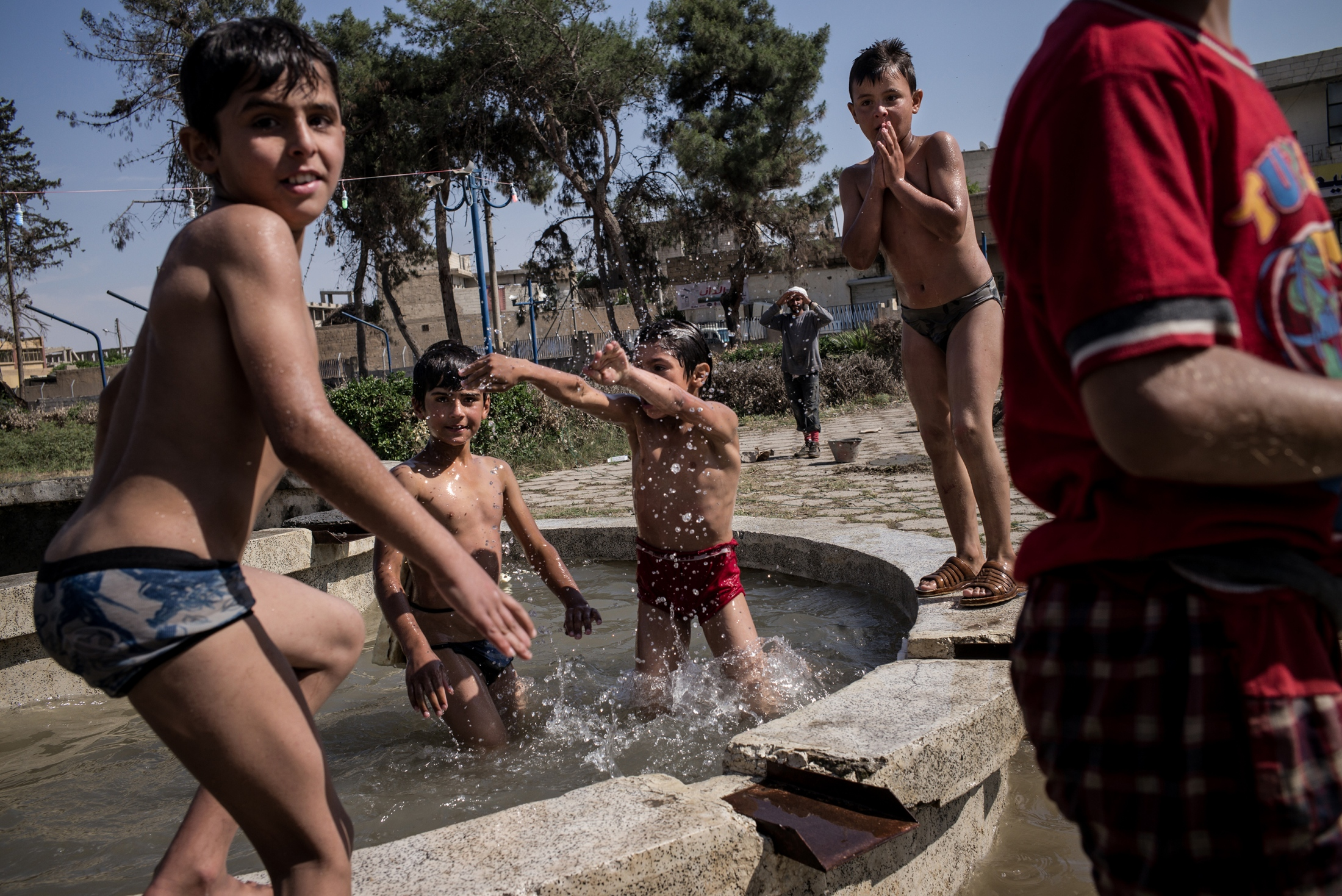Young boys swim and play in a fountain in a park in Raqqa, Syria, on Friday, May 11, 2018. Public parks in Raqqa were used as impromptu burial sites for those killed in executions carried out by ISIS during their reign, or airstrikes by the coalition during the offensive to oust the extremist group from the capital of their so-called caliphate. Many parks still contain the remains of hundreds of people, as well as unexploded ordinance. But as life comes back to this eastern Syrian city, rather than be deterred, civilians are eager to have some semblance of normal life and enjoy their freedom outdoors.