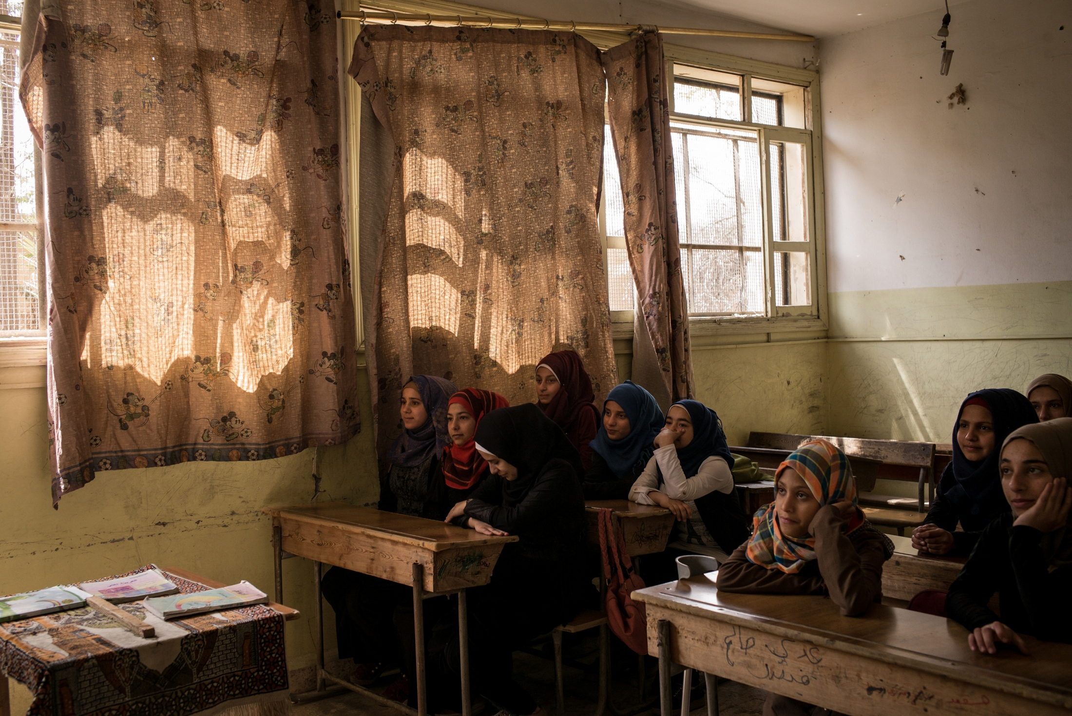 Female students are seen in class at the heavily damaged Hawari Bu Medyan School, in Raqqa, Syria, on Thursday, May 10, 2018. The school is located opposite a building that was used by ISIS's religious police, the Hisba, and was also the site of intense fighting during the offensive to retake the city from the extremist group. The school reopened in January 2018.