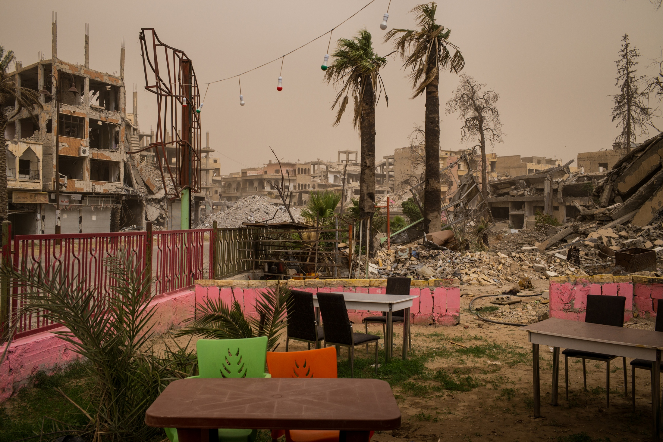 A newly opened cafe stands in contrast to the backdrop of a destroyed city in Naim Square, Raqqa, Syria, on Thursday, June 28, 2018. Naim Square  was a hub of social life before it became a symbol of ISIS's brutality, where the extremist group would carry out public executions.