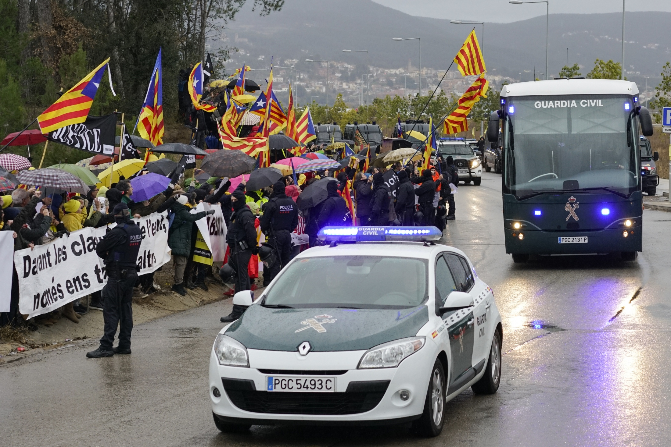 (AP Photo/Daniel Cole)  Demonstrators wave esteladas or independence flags as a bus of the Spain's Civil Guard carrying the nine Catalonian politicians and activists, leaves the Brians II prison, in Barcelona, Spain, Friday, Feb.1, 2019. Spanish authorities transferred nine politicians and activists on Friday from prisons in Catalonia to the country's capital, Madrid, ahead of a high-stakes trial for their part in an attempt to secede from Spain.