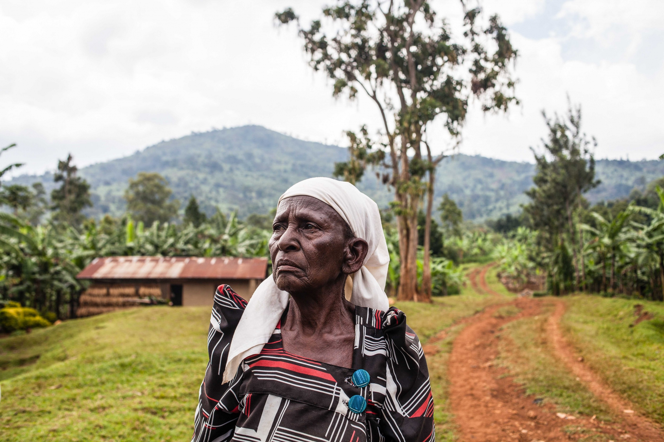 A portrait of 81-year-old Masa at her home in Bududa, Uganda. She began supporting mothers to give birth in the villages of Bududa District 40 years ago when her daughter in-law was forced to give birth in the middle of the night in the Elgon mountains in Eastern Uganda. In 2010, the government banned the practice of Traditional Birth Attendants (TBAs), but did little to improve modern maternal health services in rural areas of Uganda. Masa now refers her patients to the health facility in Bushiika town, Bududa District, Uganda.