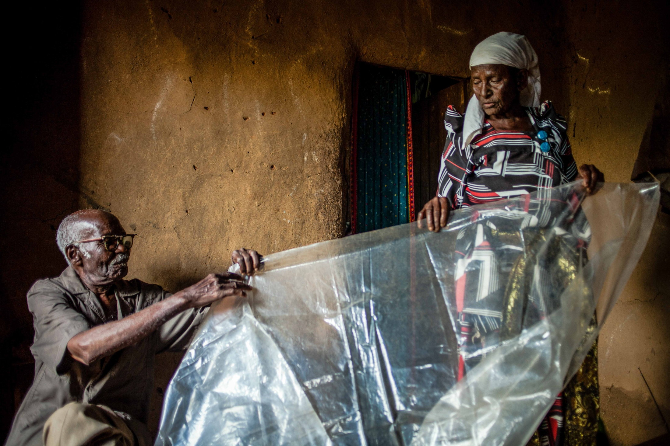 Masa 81, shows the only tool she has available when assisting in deliveries – a plastic sheet that she lays down in her living room in Bududa to protect infants from the unsterilized ground. This is a sharp contrast to the tools used in deliveries at the rural health center in Bududa, Uganda. In 2010, the government banned the practice of Traditional Birth Attendants (TBAs), but did little to improve modern maternal health services in rural areas of Uganda. While Uganda's maternal mortality rate has declined in recent years, women in rural areas still suffer disproportionately from a lack of medical services. In northern Uganda, a woman has a one-in-25 lifetime chance of dying in childbirth.