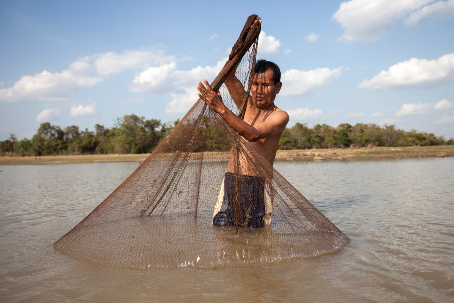 Por Lua Banlua Nikom, 68, catch fish in Huay Thong, next to his village. If the mining company expands the locals fear that the water will become badly salinised due to the waste by-product of potash mining is salt and that the fish will die.