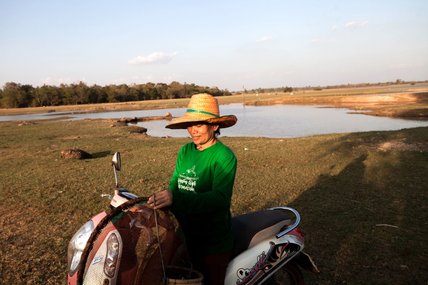Ratawan Panta, 43, returns to her house on her motorcycle after an afternoon of catching shellfish and shrimp in the lake behind her. She wears the communities anti-potash mining shirt that has become symbolic with their struggle against a Chinese potash mining company.