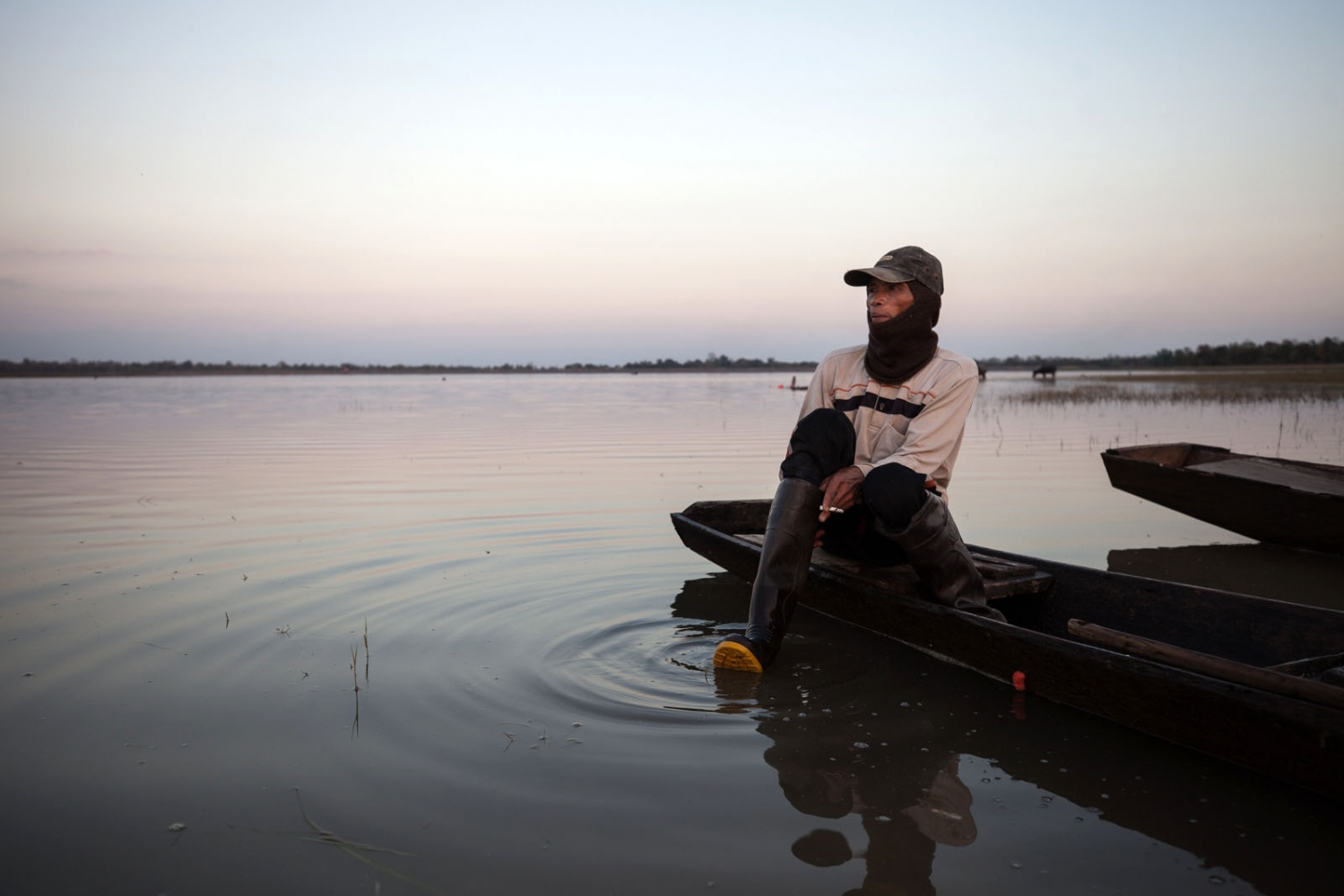 A fisherman returns to shore at dusk after placing his nets in Huay Thong Lake. He will return to collect the fish the next morning.