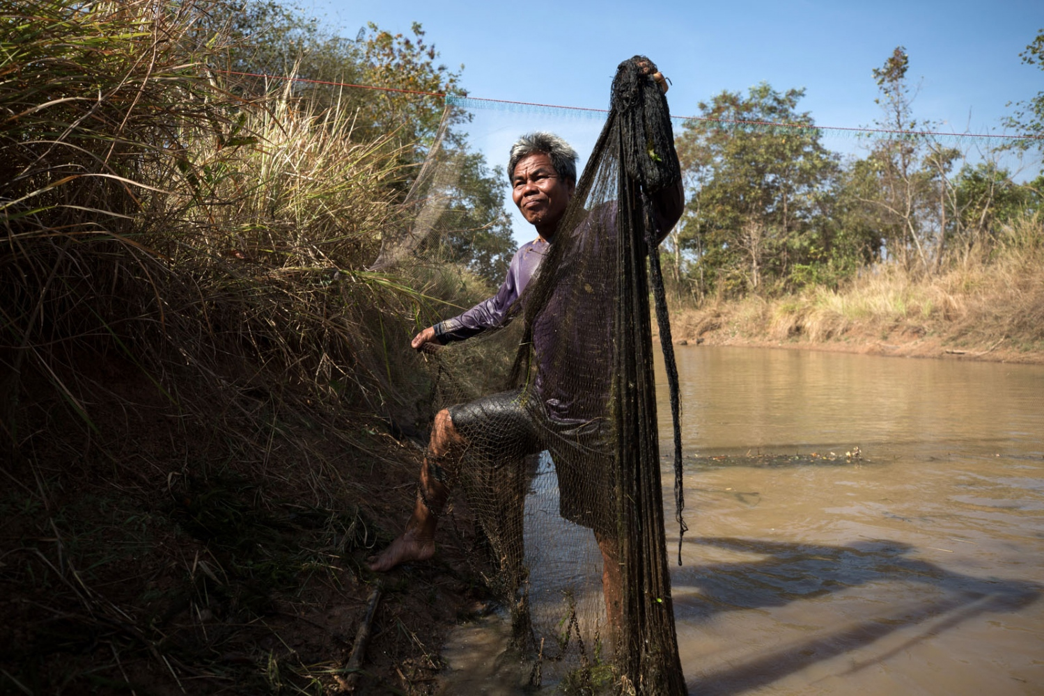 Por Dui, 51, uses his net to catch fish and crabs in a small canal that runs from the main lake in their community.