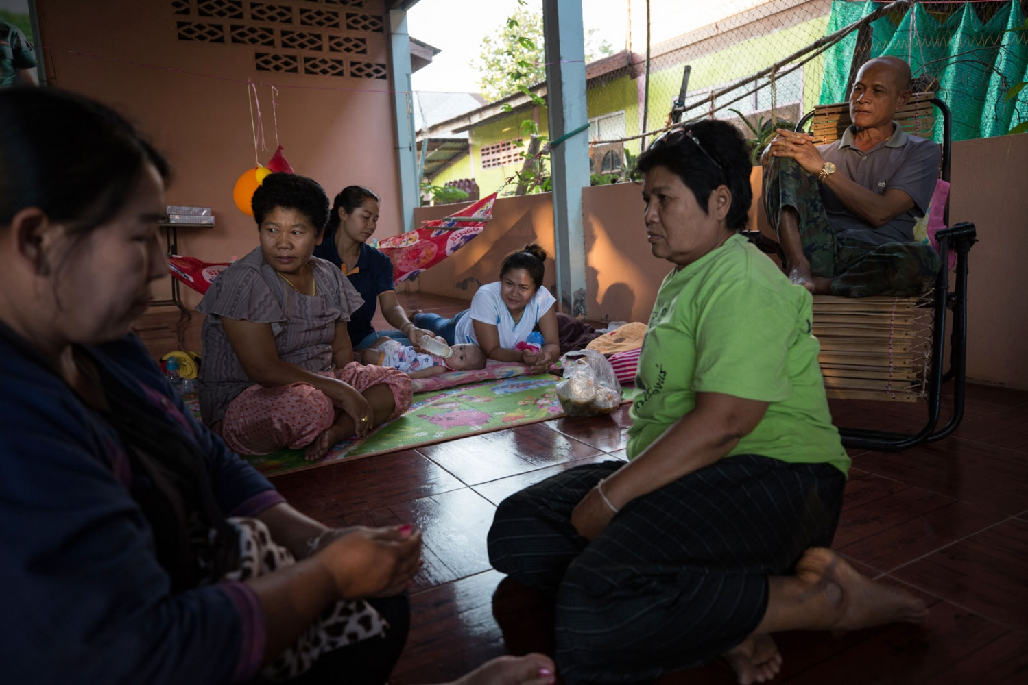 Neighbours and family members sit and chat at Mae Ding's (second left) house in Ban Wang Bong Noi.