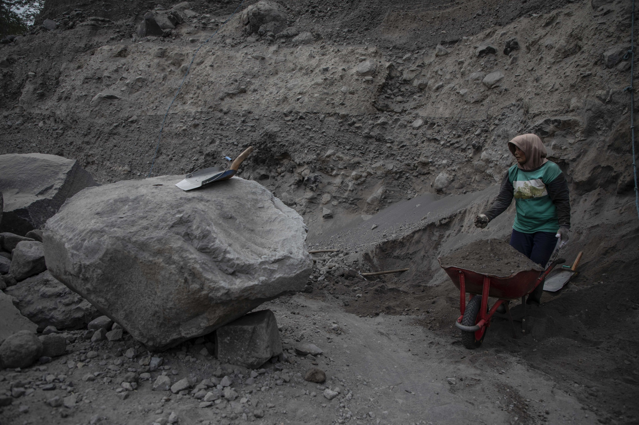 Mbah Pausen, 43, starts to work in a sand mine on the mountain every day at 06.00am. She finishes at 3.00pm to take care of her family, having only Friday and Sunday off. 'The work is very heavy but I have no other choice in life,' she says. As her parents worked as sand miners, she began this work at the age of 6. She know that she is at risk of being buried by a landslide each day. 'If you can, don't work here,' she continues, and yet she plans to work here until she can't anymore. She is the only woman working in this sand mine, lives about 6 miles from the mountain, and earns earning 30000 - 50000 Indonesian rupiah a day (2 to 3.30 US Dollar