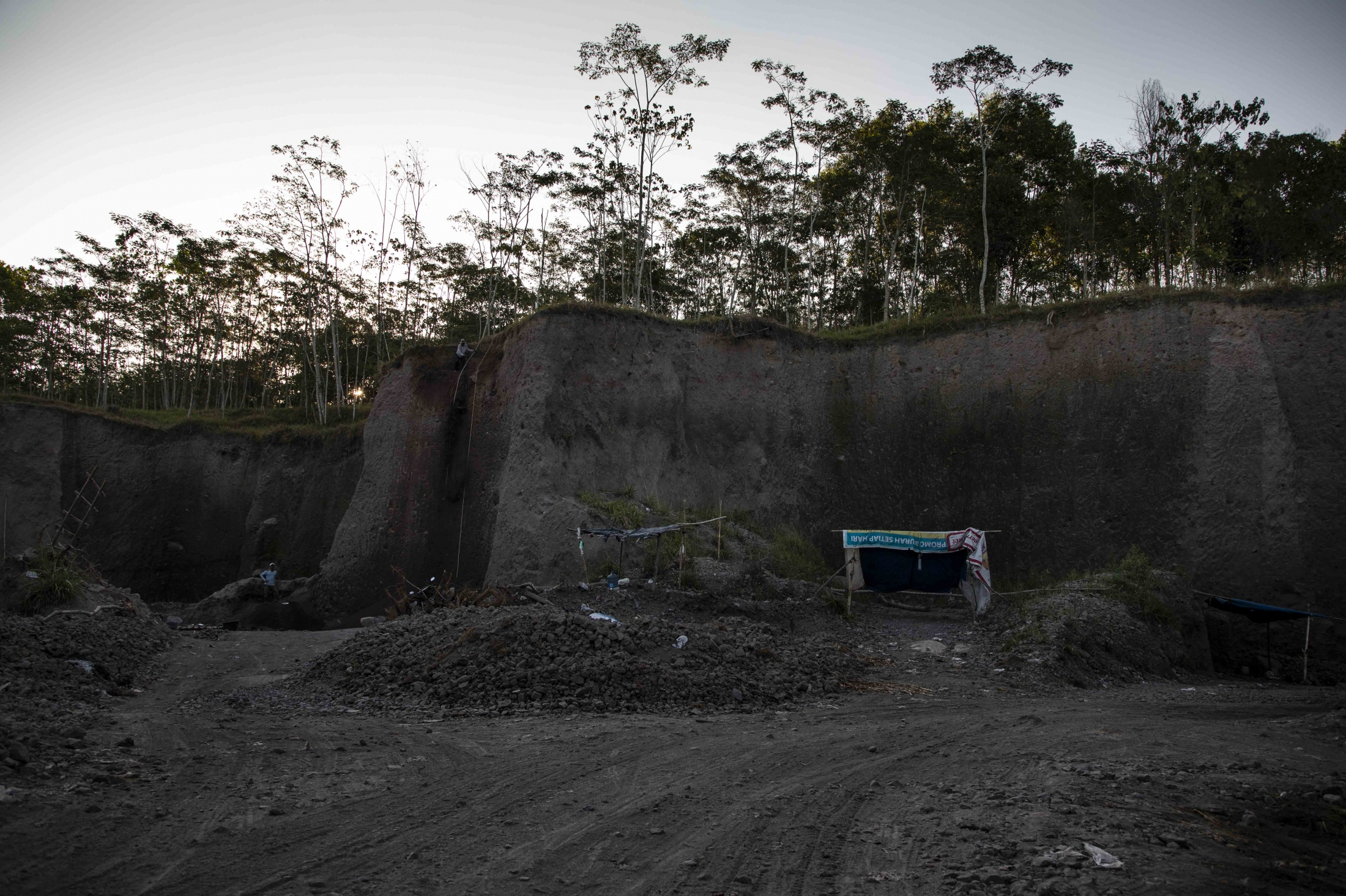 A sand-mining ground on Mount Merapi. In recent years, illegal sand mining has become a controversial reality of mountain life. In the past, locals would often manually - and legally - mine the location which naturally limits the amount of sand they are able to obtain. This is even necessary due to the amount of sand the volcano produces when erupting. However, large-large-scale mining activities by non-locals have developed after 2010 and continue to take place despite lack of authorization by the government. Scientists are certain that this severely threatens Merapi`s lava embankments. Locals for whom the mountain is sacred, believe it will anger the ancient Javanese spirits inhabiting it and cause further eruptions.