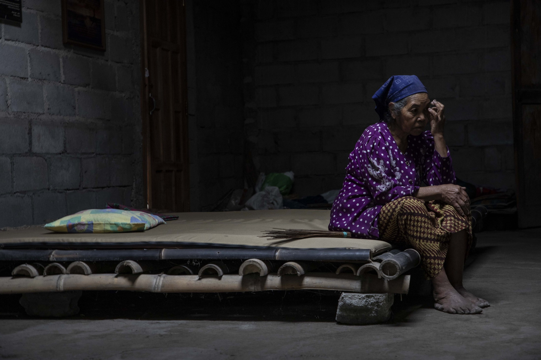 Mbah Sudiwiyono taking a break on the bed in her one-room house in the forest near the volcano crater. The walls and roof were rebuilt after the 2010 eruption. As the only remaining inhabitant of her village, she sometimes misses her family and neighbours at these quite hours after finishing all work. Yet, she feels more comfortable living here in the place where she was born and lived in for almost all her live.