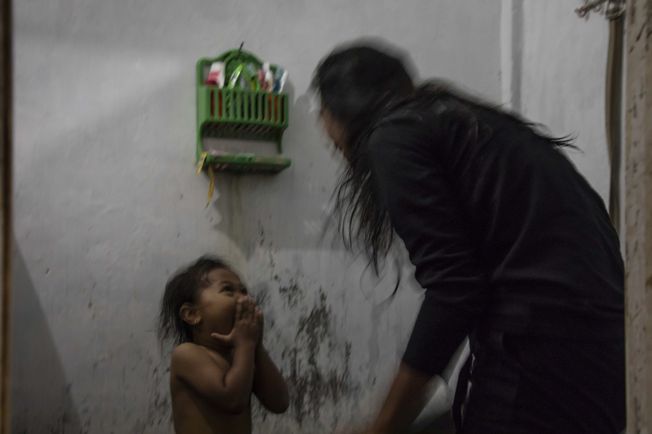 Mbak ('sister'/young woman) Barni, 24 years, showering her daughter in their house in th viillage of xy. She lives here with her husband but frequently visits her mother who now lives in Karang Kendal. Barni grew up in Palemsari but went to school in a city far away from the mountain for 6 years. Yet, she decided to return to the mountain after high school because of the dedication of people to nature here, their respectful caring of others, and their unique and deep cultural roots. Although she will also ensure her daughter receives a very good education, she hopes that she will live close to the mountain later in her life.