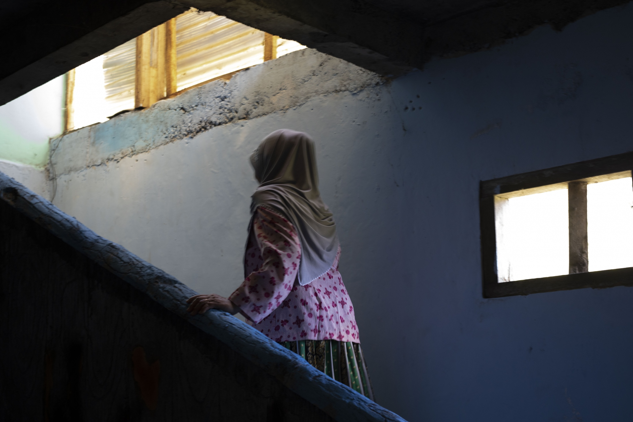 Mbah Parish walks up the stairs in her house. It is simple but new like all in the relocation village of Karang Kendal.