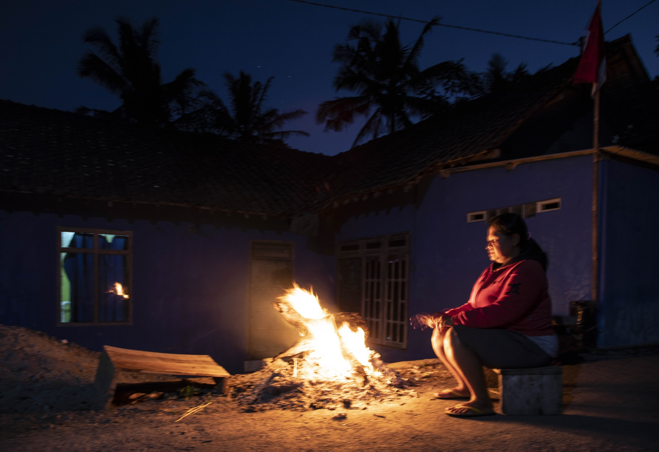 Rusmiyati, 45, sits by a fire in the evening, near the ruins shown in the previous picture. She refuses to move to a relocation village as she feels that the high risk zone continues to be her home. Traditionally the 'home' of the women living on Merapi was the place where they would live and work. For the relocated, the relocation village has become their home, however, with no land that belongs to them, their former land has become a place of work.