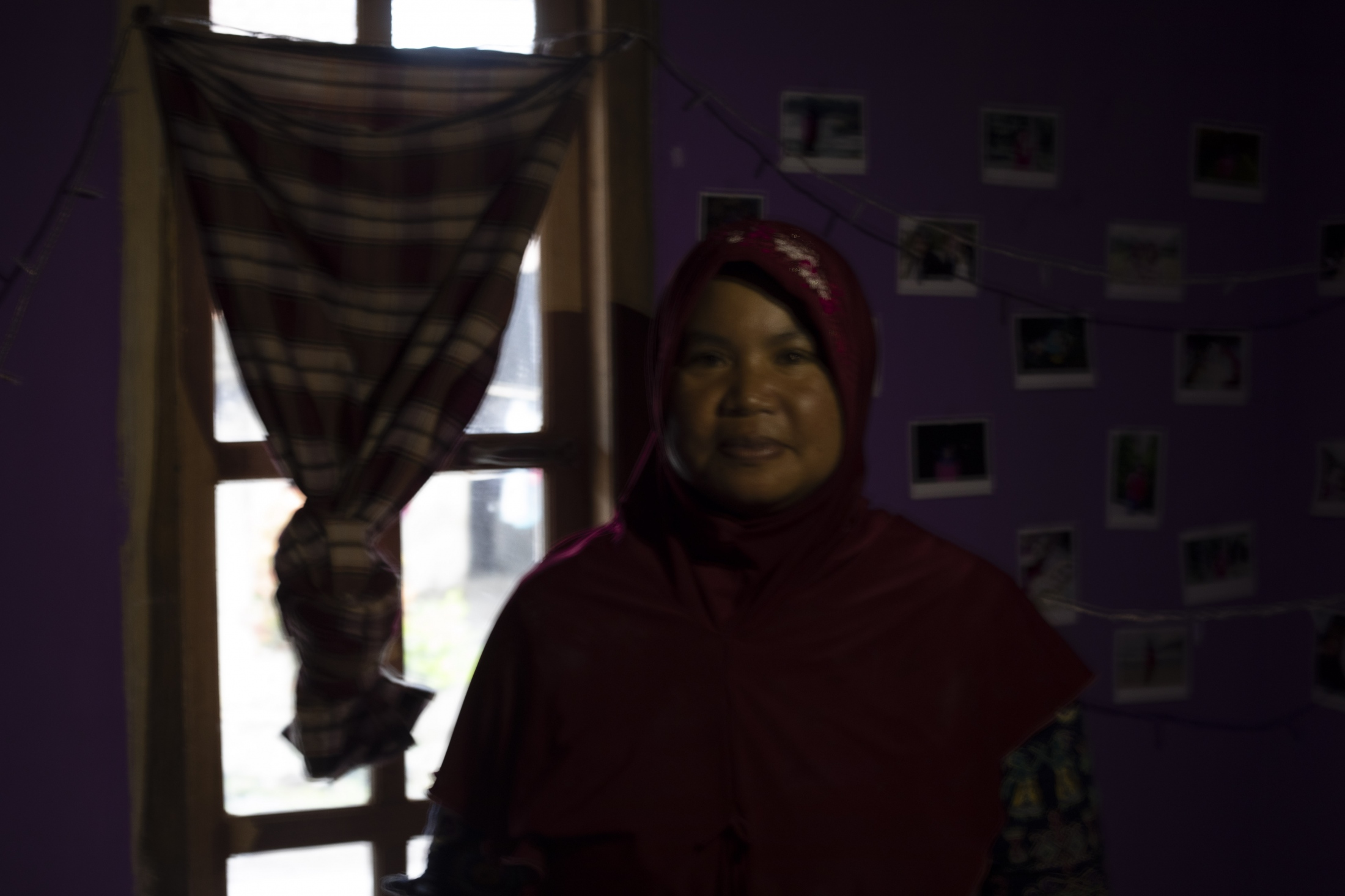 Mbah Srirahayu, 41, portrayed in her new home in the village of Karang Kendal. She lost her brother, sister, and niece in the devastating volcanic eruption in 2010 (that killed 353 people). Survivors like her - in total about 80 families - that previously lived in Palemsari were relocated here in past years. She greatly respects the mountain and like believes that respecting the spirits, taking care of the environment, and of people are the only way to be free from fear of living close to it.