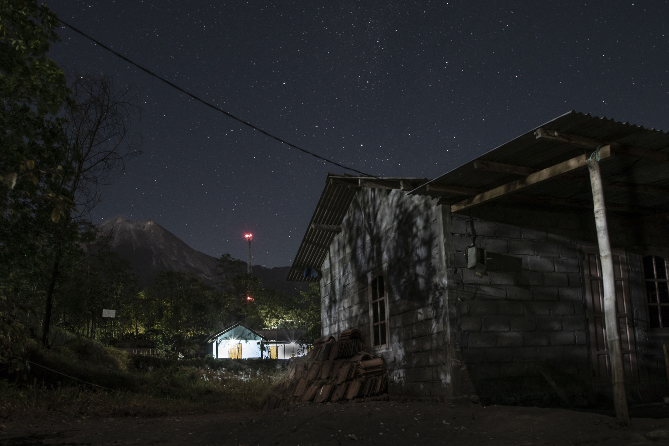 A view of Mount Merapi at night. Rarely can one see the volcano crater and the stars in the sky. Most of the time, Merapi is covered by clouds due to its high elevationof about 9,600 ft. When one can see it like this it seems as if the most active volcano of Indonesia is slowly breathing. Locals therefore think of it as a living creature, one that needs to be respected. To keep the volatile natural phenomena in balance, prayer and spiritualism are key to people living by the mountain.