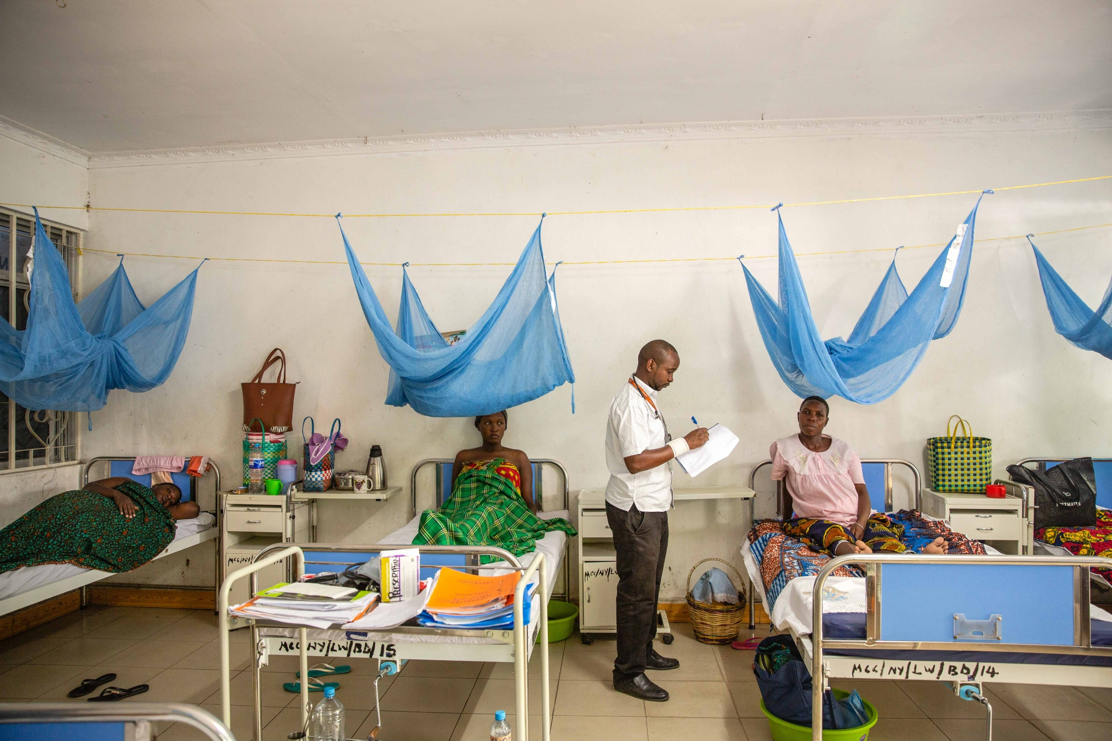 Dr. Chris Paul Tabalo, a Doctor checks on expectant women awaiting delivery in the maternity ward at Nyamagana hospital, Tanzania. For The Aga Khan Foundation.