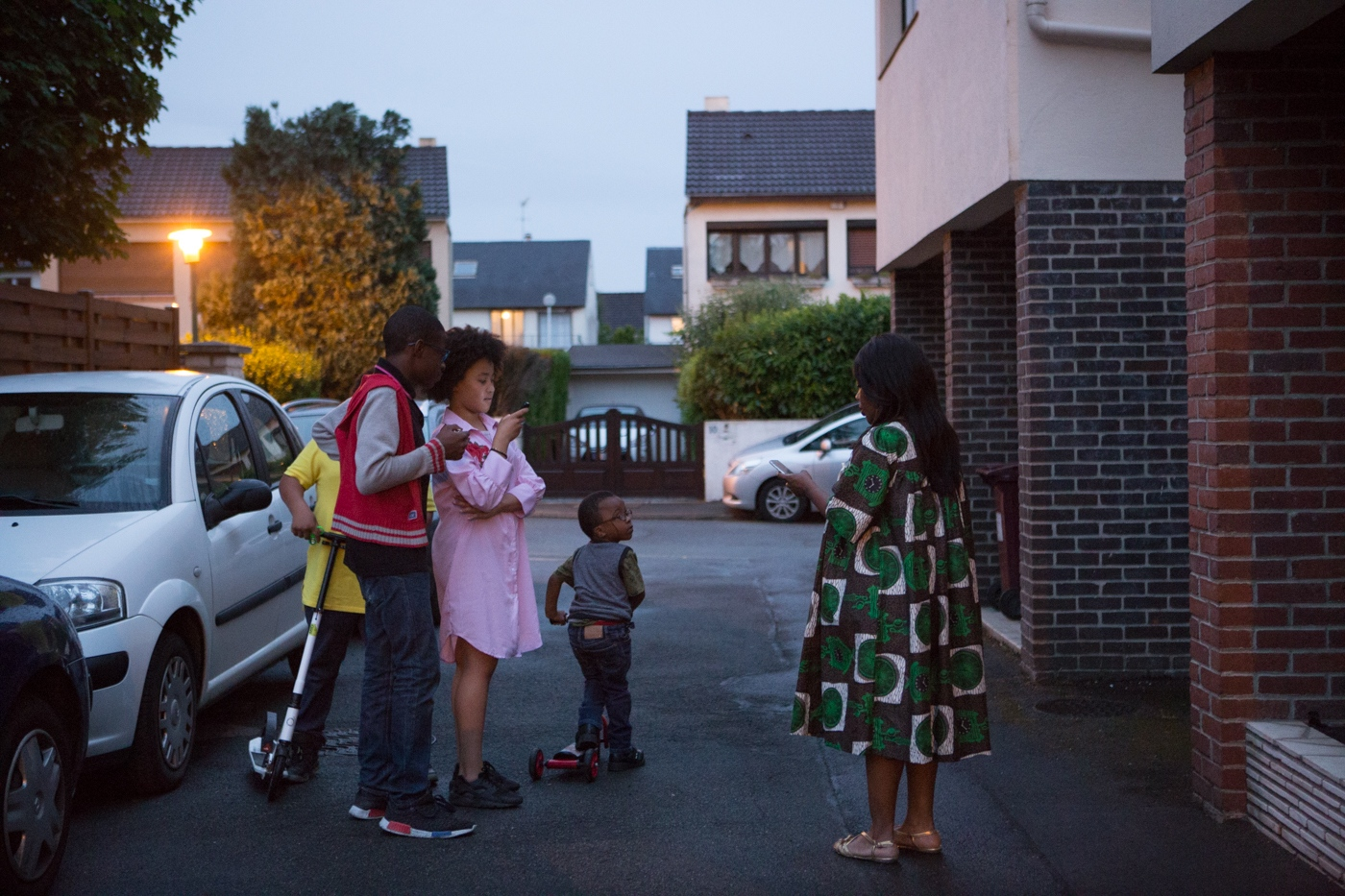 Corinne Kyoto Sy and kids in front of her house during the mourning of her father. For the first generation of afro-french women finding their place as a mixed culture in a traditional country as France is a deep challenge. Raised in the African culture of their parents and with a strong influence from the European environment and education. For their kids, the second generation to come, the feeling of belonging will be more present and natural. Livry-Gargan, Ile de France, France