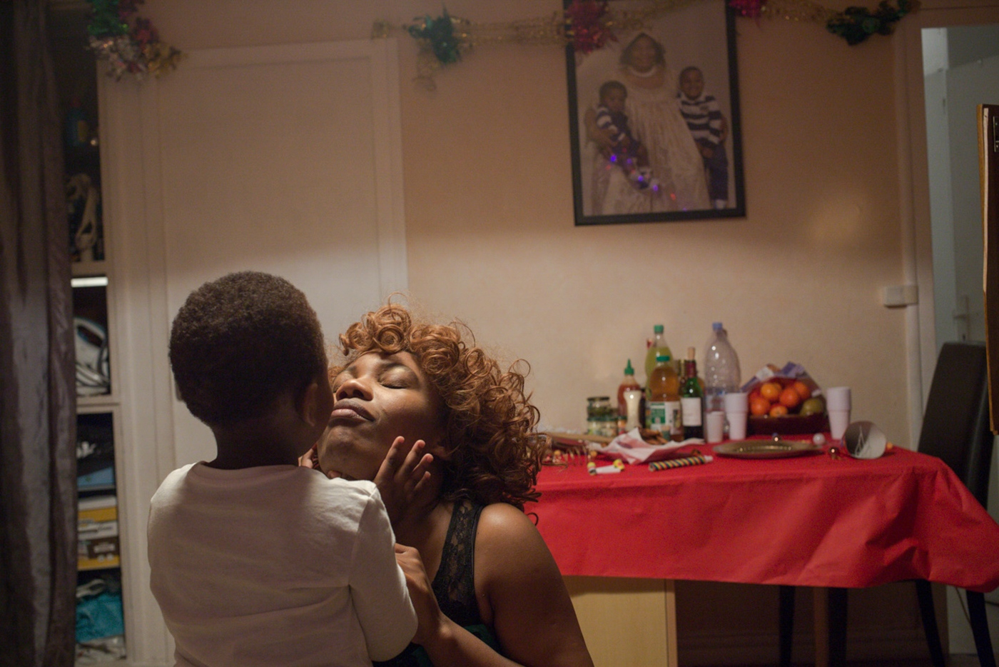 Corinne Kyoto-Sy kissing her son, Kesyah, during New Years' Eve in Bondy, in the northern suburbs of Paris. Corinne is a caregiver. By this moment, single mother and living with her mother in Bondy village.
