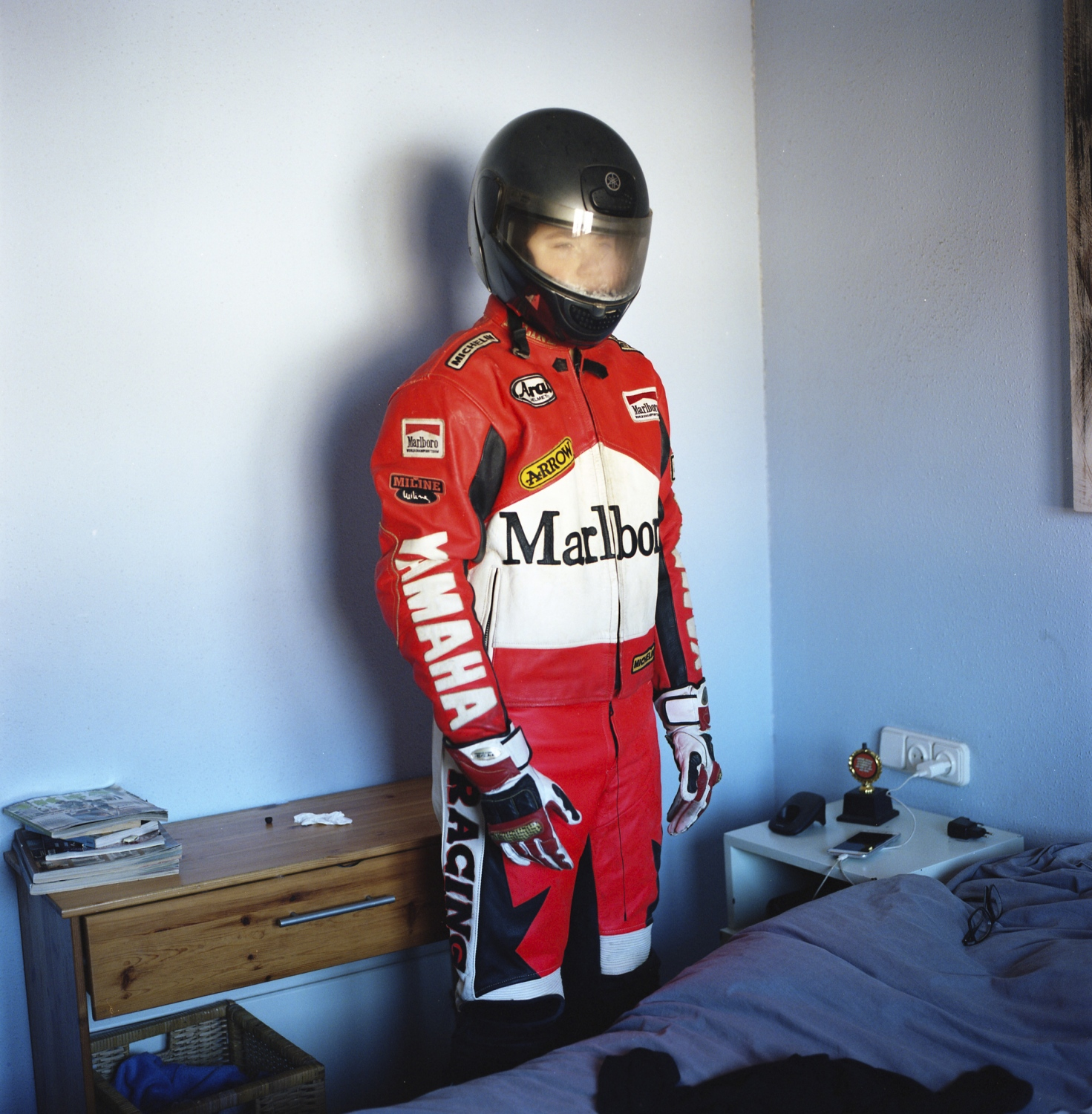 "Jose's fifteen-year-old son, Josep, wears his father's motorcycle test pilot suit in his parent's room. In a past life Josep's father was a test pilot at Catalonia's Montmeló race circuit tasked with racing prototype models around the track before they were deemed safe to use in official races. Like his father, Josep wants to follow in his footsteps to become the eighth generation locksmith in his family. ""As a boy I used to go to work with my dad and see how his work made people feel safe in their homes."" Josep plans to leave school next year in order to work fulltime with his father."